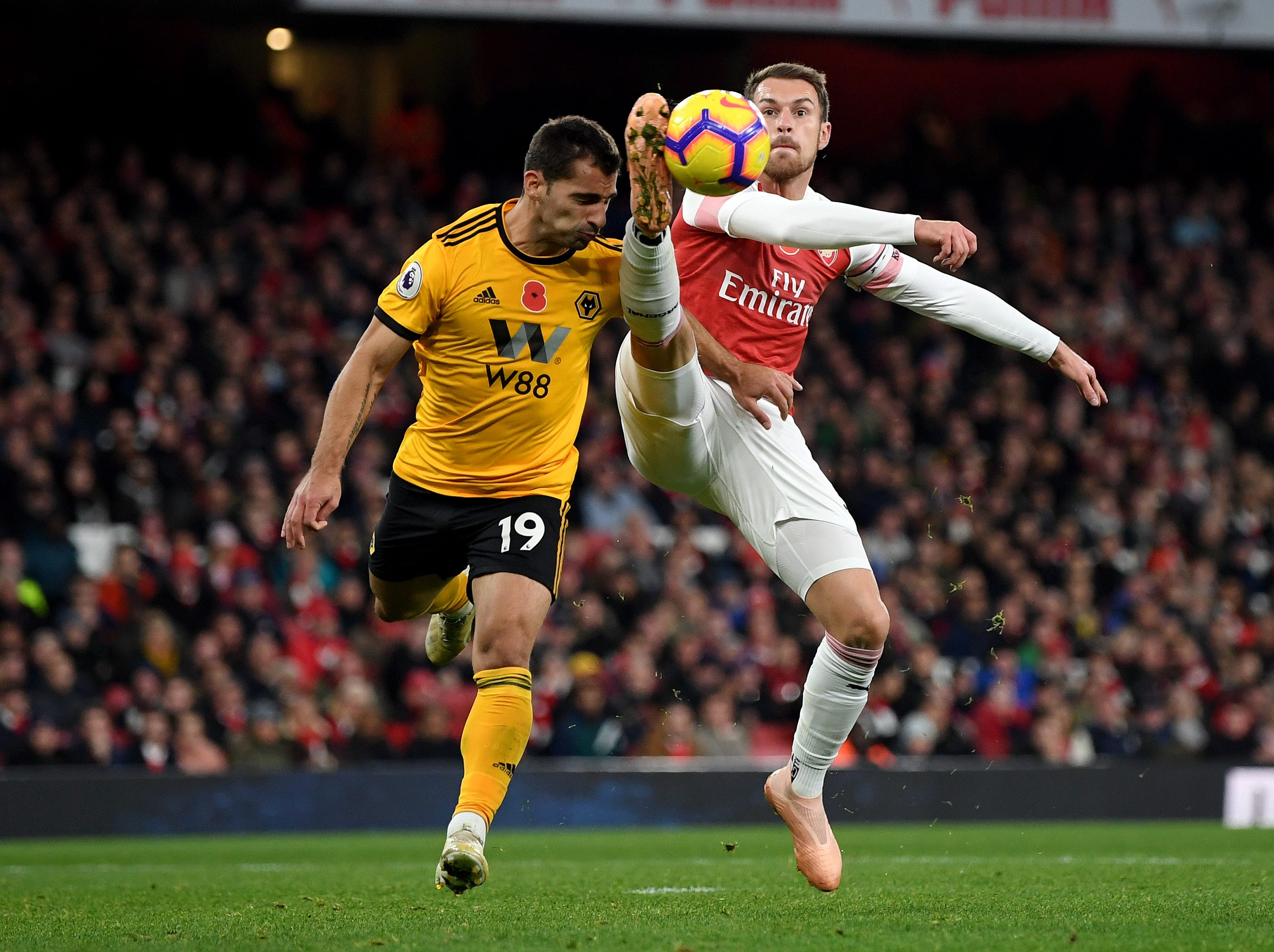 Arsenal's Aaron Ramsey controls the ball in  while being challenged by Jonny Otto of Wolverhampton.