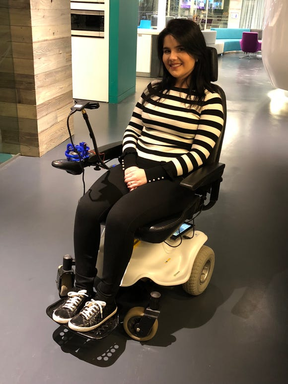This young woman sits in a wheelchair that can be controlled with a smile through the Wheelie 7 AI kit.