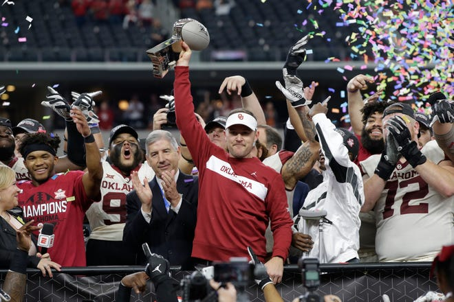 Oklahoma head coach Lincoln Riley holds up the Big 12 championship trophy after the Sooners defeated the Texas Longhorns on Saturday.