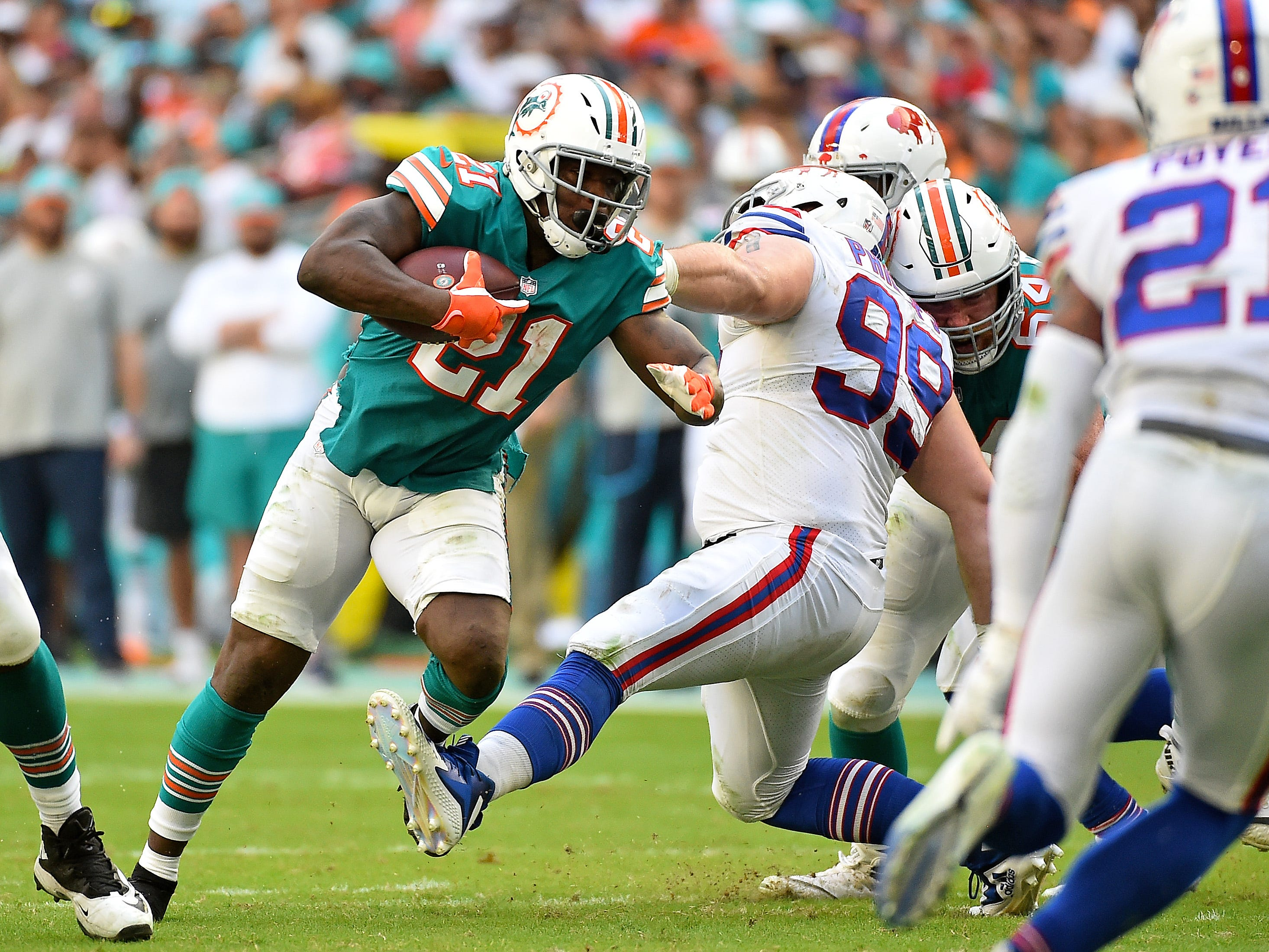 Buffalo Bills defensive tackle Harrison Phillips (99) trips Miami Dolphins running back Frank Gore (21) during the first half at Hard Rock Stadium.
