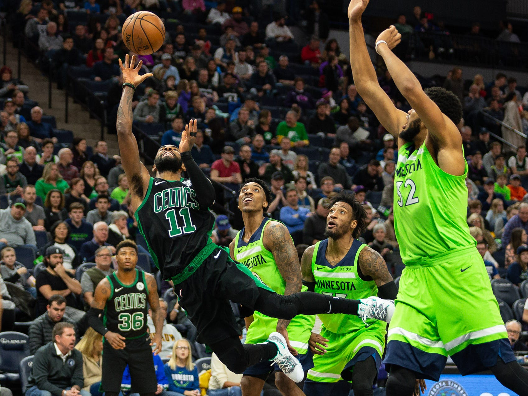 Dec. 1: Celtics guard Kyrie Irving (11) goes careening down the lane past a trio of Timberwolves defenders during the second half in Minneapolis.