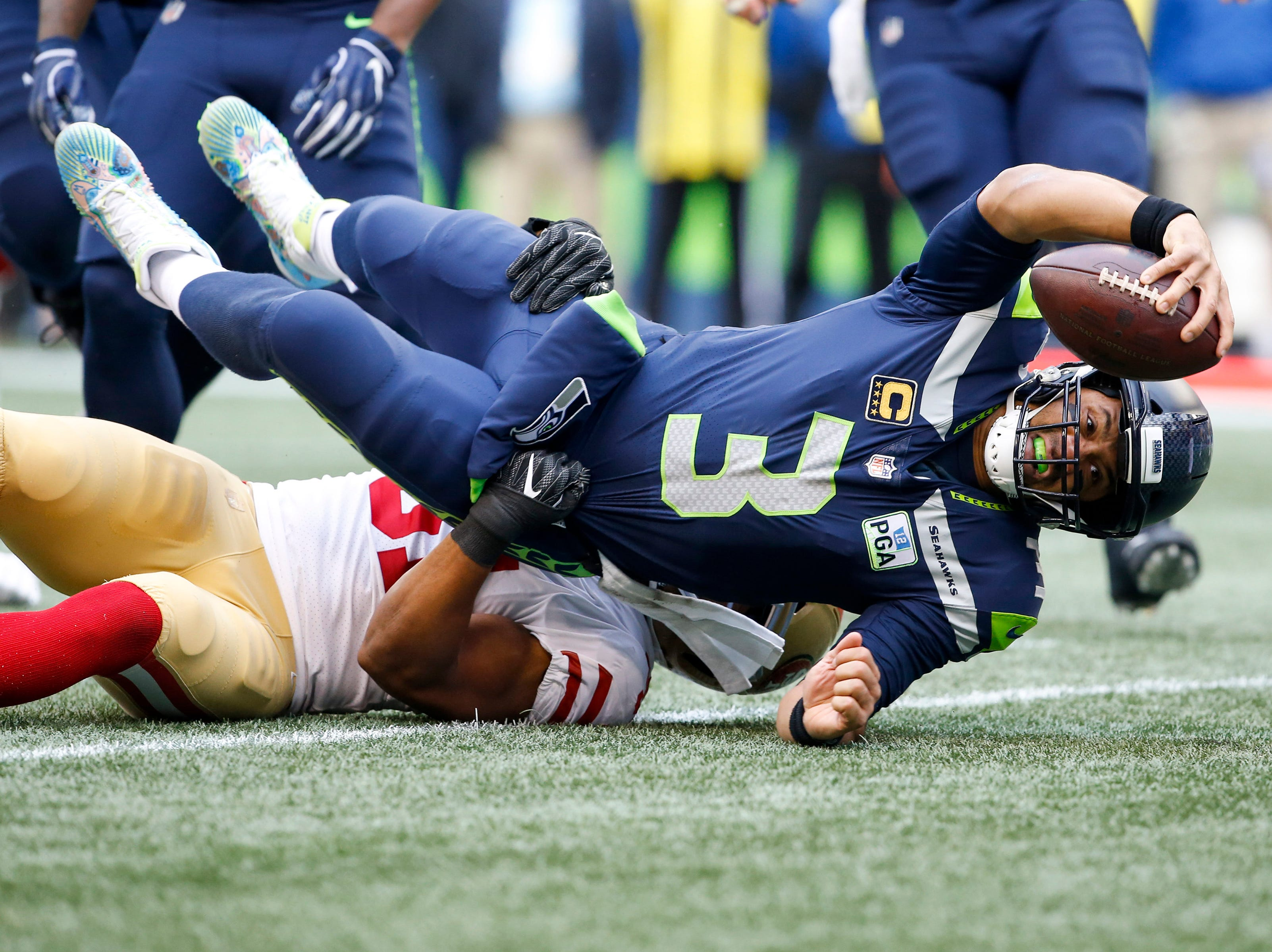 Seahawks quarterback Russell Wilson stretches out for extra yardage on a rushing attempt against the 49ers.