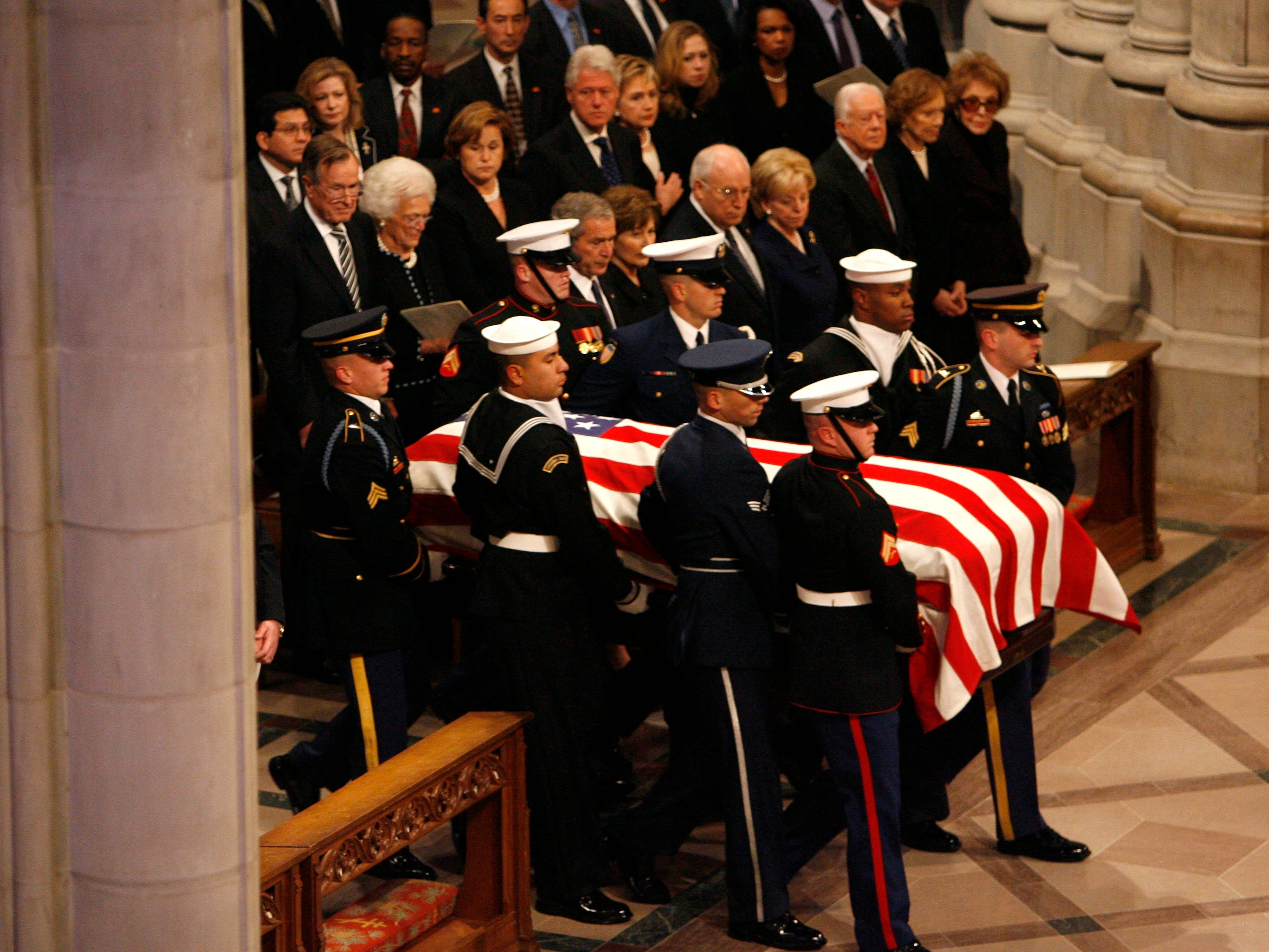 A military honor guard carries President Gerald Ford's casket past President Bush and former presidents and first ladies for the funeral at the National Cathedral, Jan. 2, 2007, in Washington.
