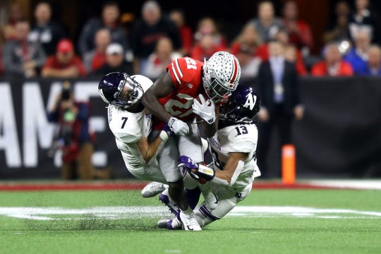 Ohio State Buckeyes wide receiver Parris Campbell (21) is tackled by Northwestern Wildcats defensive back Travis Jack Whillock (7) and defensive back JR Pace (13) in the first half in the Big Ten conference championship game at Lucas Oil Stadium.