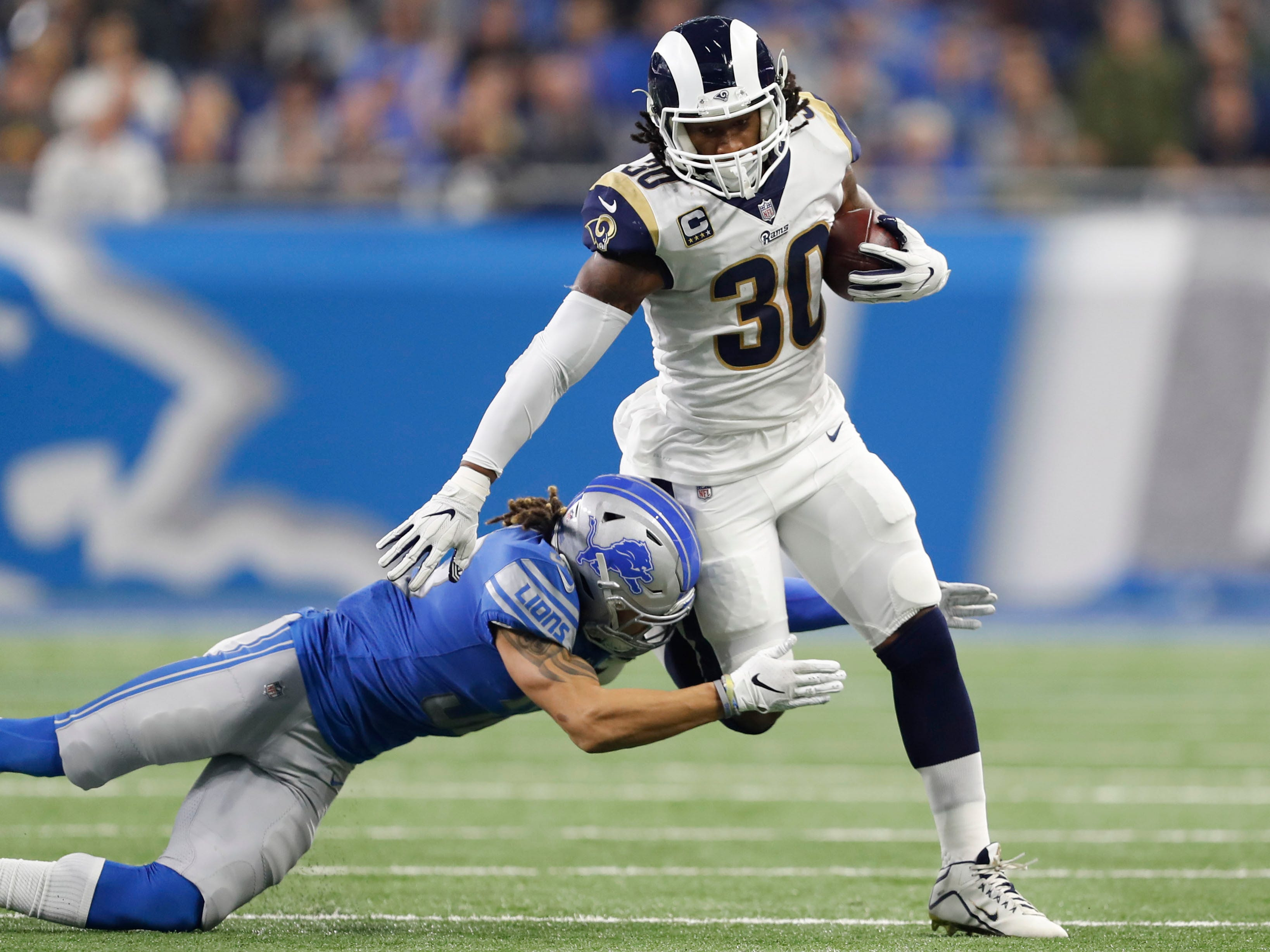 Los Angeles Rams running back Todd Gurley (30) runs the ball against Detroit Lions defensive back Mike Ford (38) during the first quarter at Ford Field.