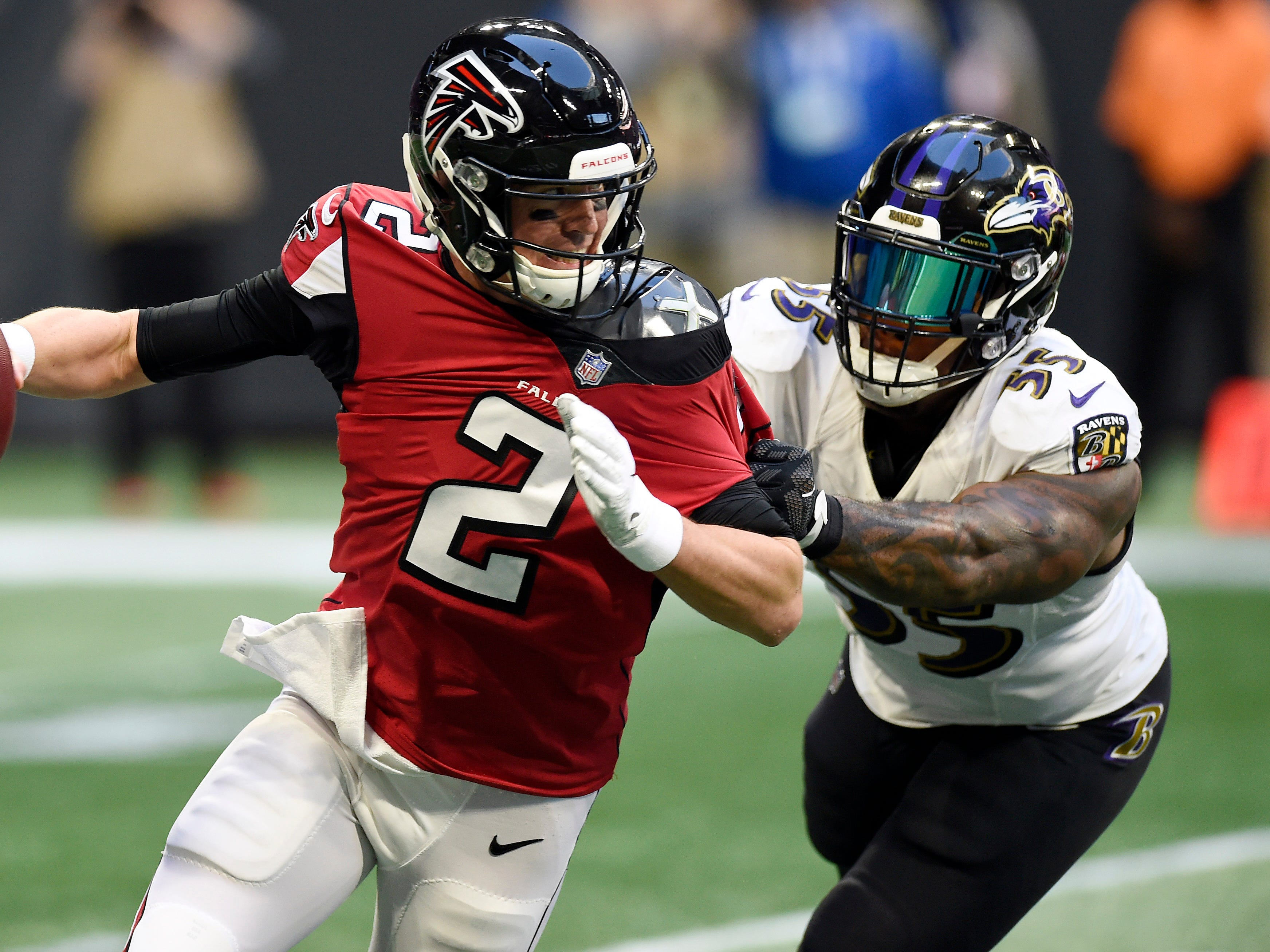Atlanta Falcons quarterback Matt Ryan (2) scrambles out of the pocket under pressure from Baltimore Ravens outside linebacker Terrell Suggs (55) during the first quarter at Mercedes-Benz Stadium.