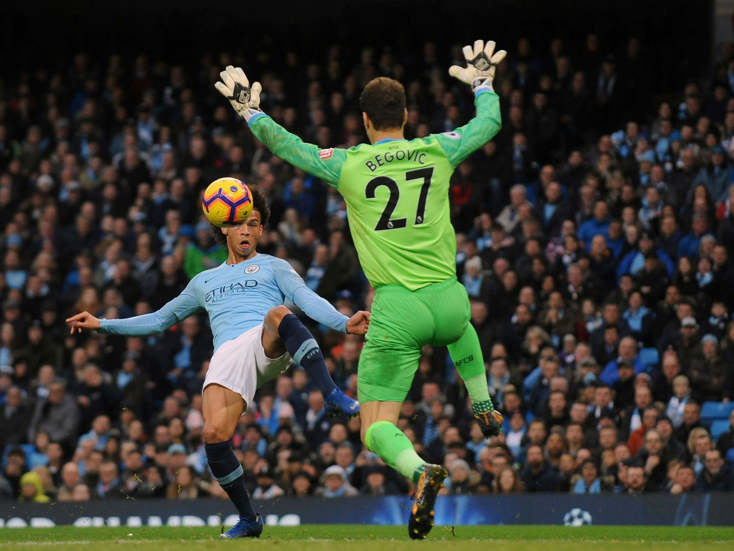 Bournemouth goalkeeper Asmir Begovic, right, makes a save in front of Manchester City's Leroy Sane.