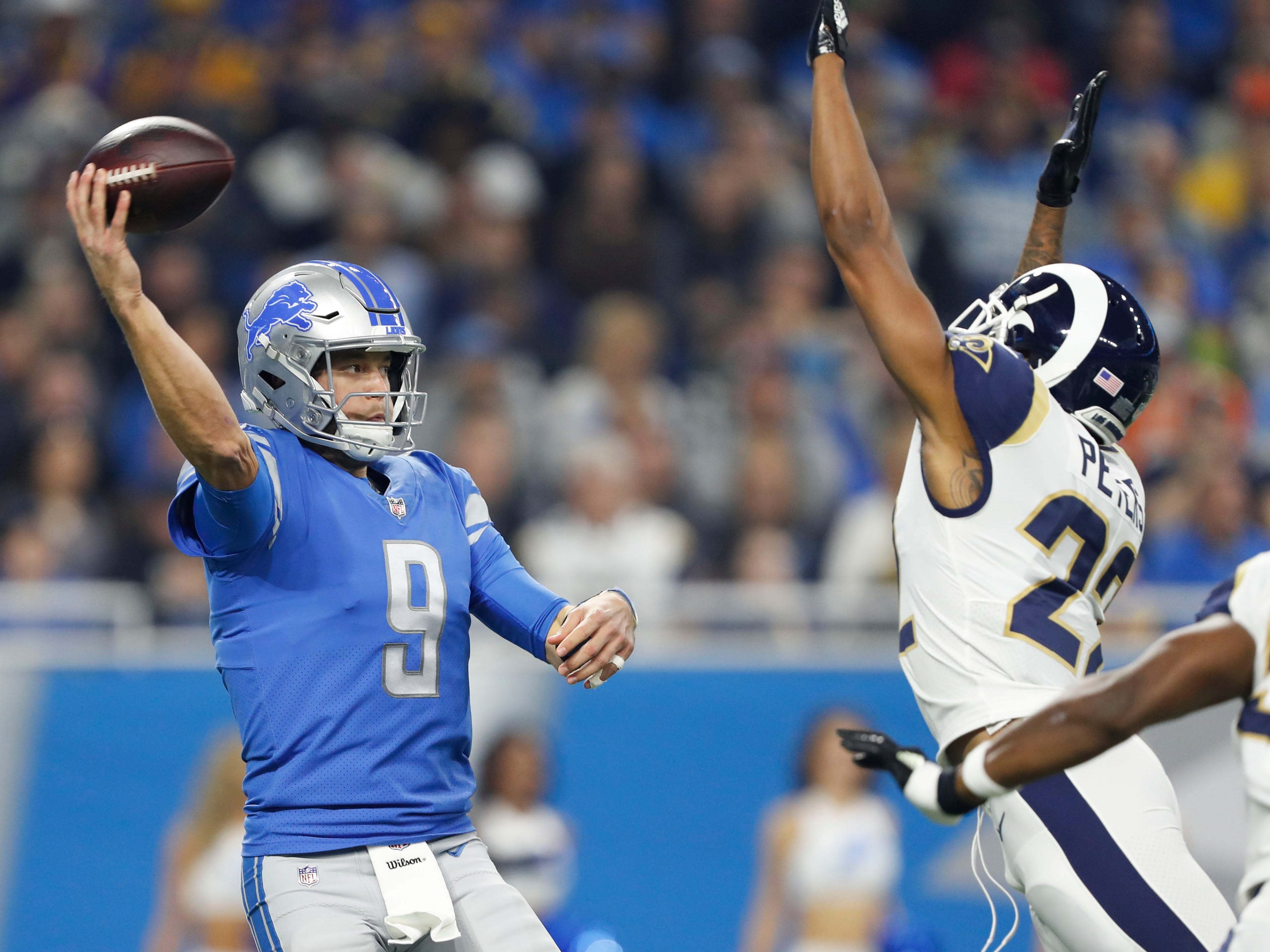 Detroit Lions quarterback Matthew Stafford (9) passes the ball against Los Angeles Rams cornerback Marcus Peters (22) during the first quarter at Ford Field.