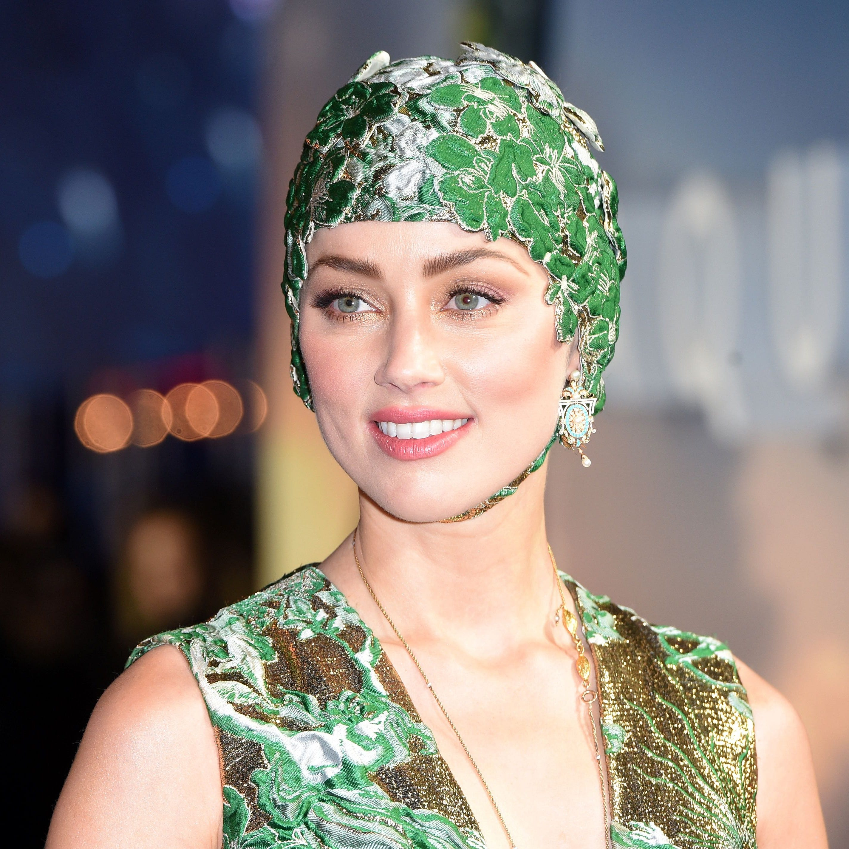 "Amber Heard wore a very fitting couture swim cap to the London world premiere of ""Aquaman."""