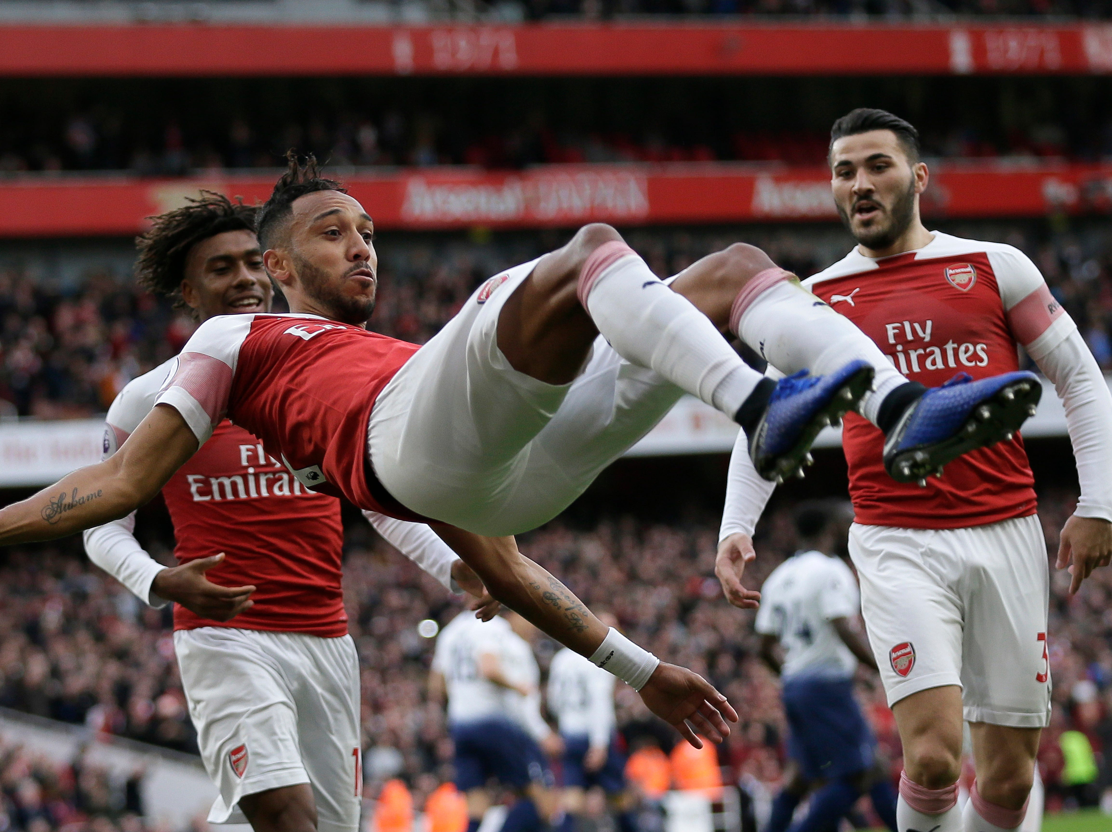 Arsenal's Pierre-Emerick Aubameyang celebrates with his teammates after scoring his side's opening goal against Tottenham.