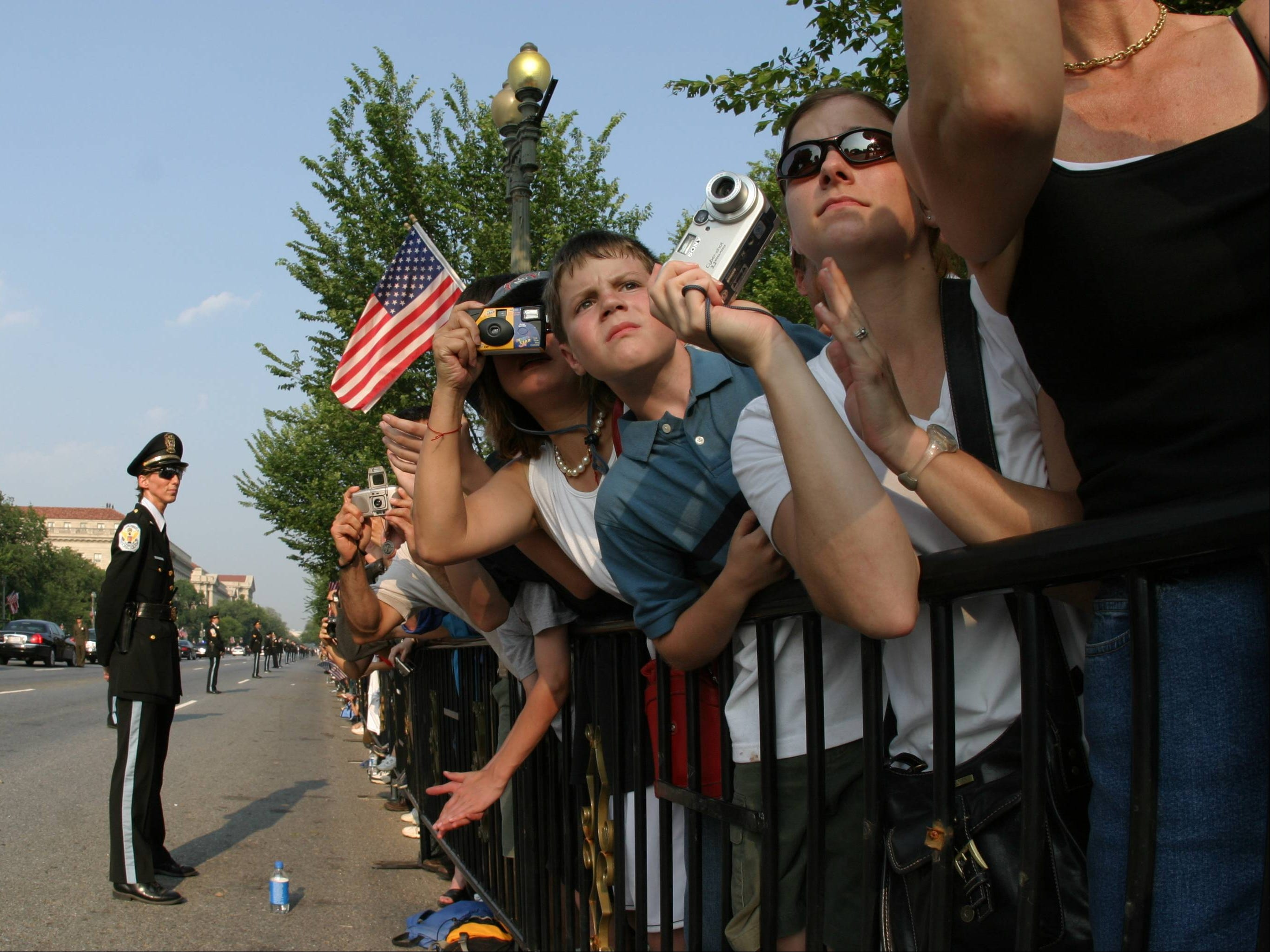 Spectators watch the coffin containing the remains of former President Ronald Reagan  placed on a caisson on Constitution Ave. near the White House, June 9, 2004, in Washington.