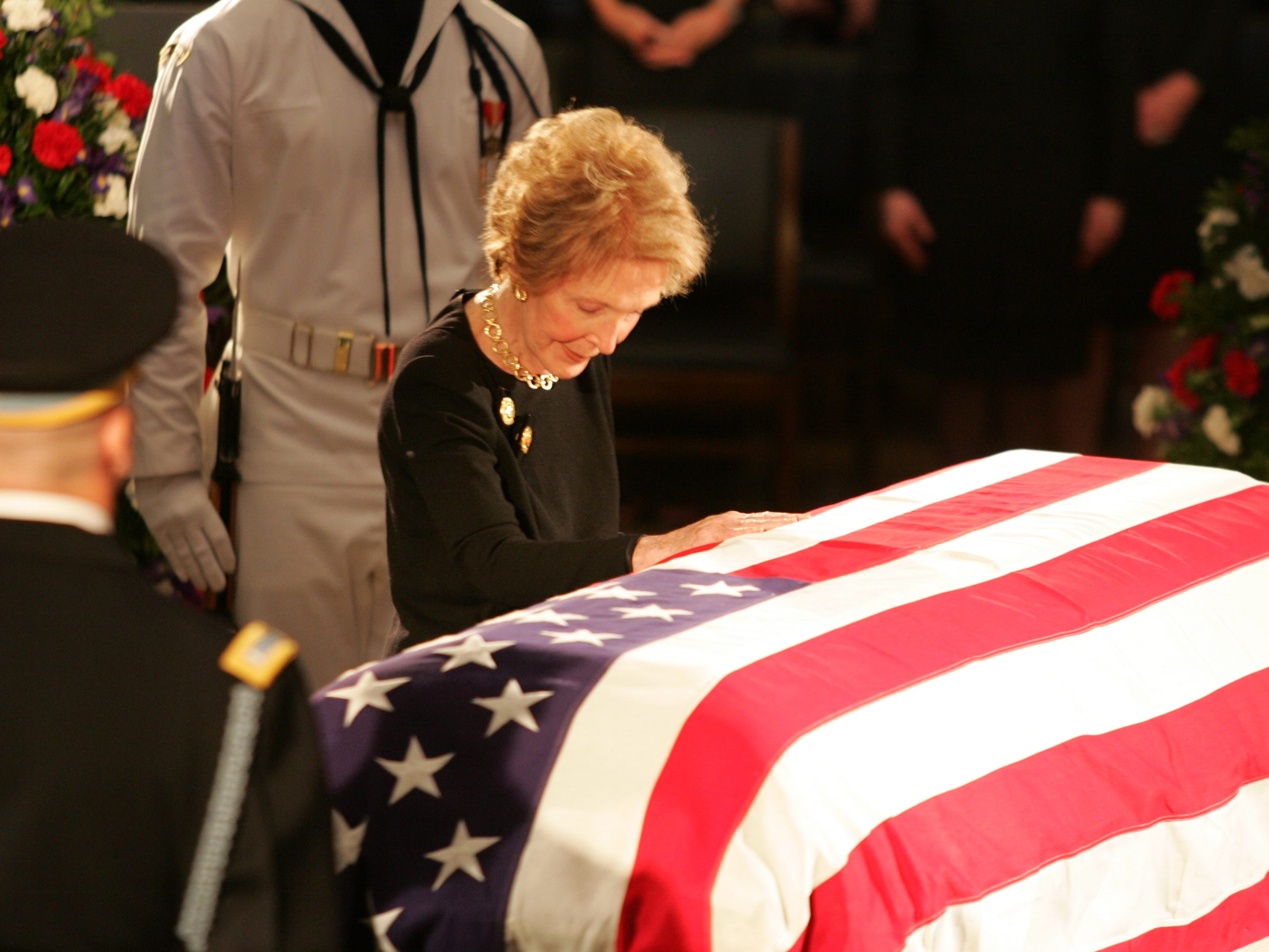 Nancy Reagan bows her head and touches the casket of her husband, President Ronald Reagan, at a service in the Rotunda of the Capitol, June 9, 2004.