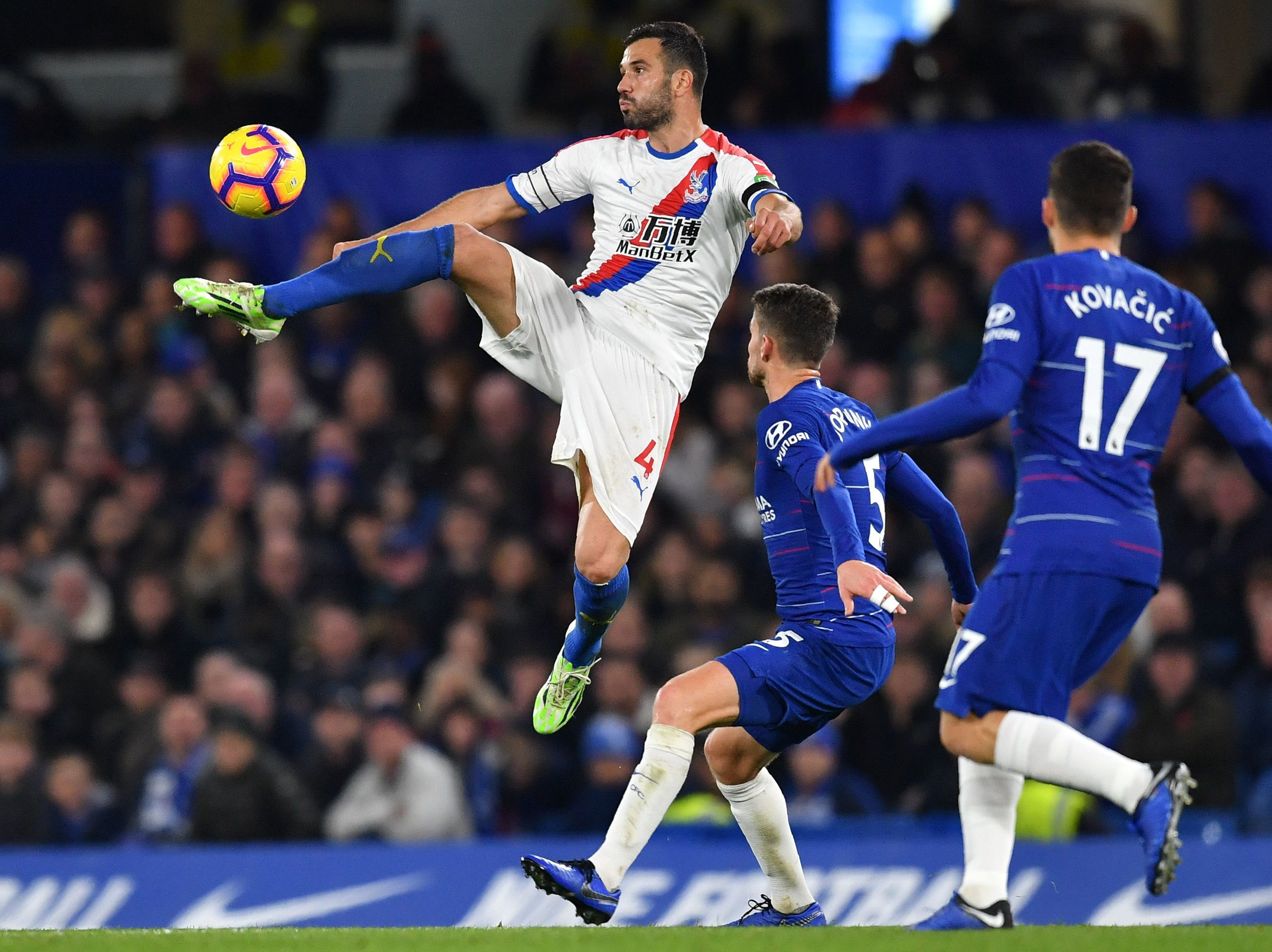 Crystal Palace's Luka Milivojevic jumps to control the ball against Chelsea.