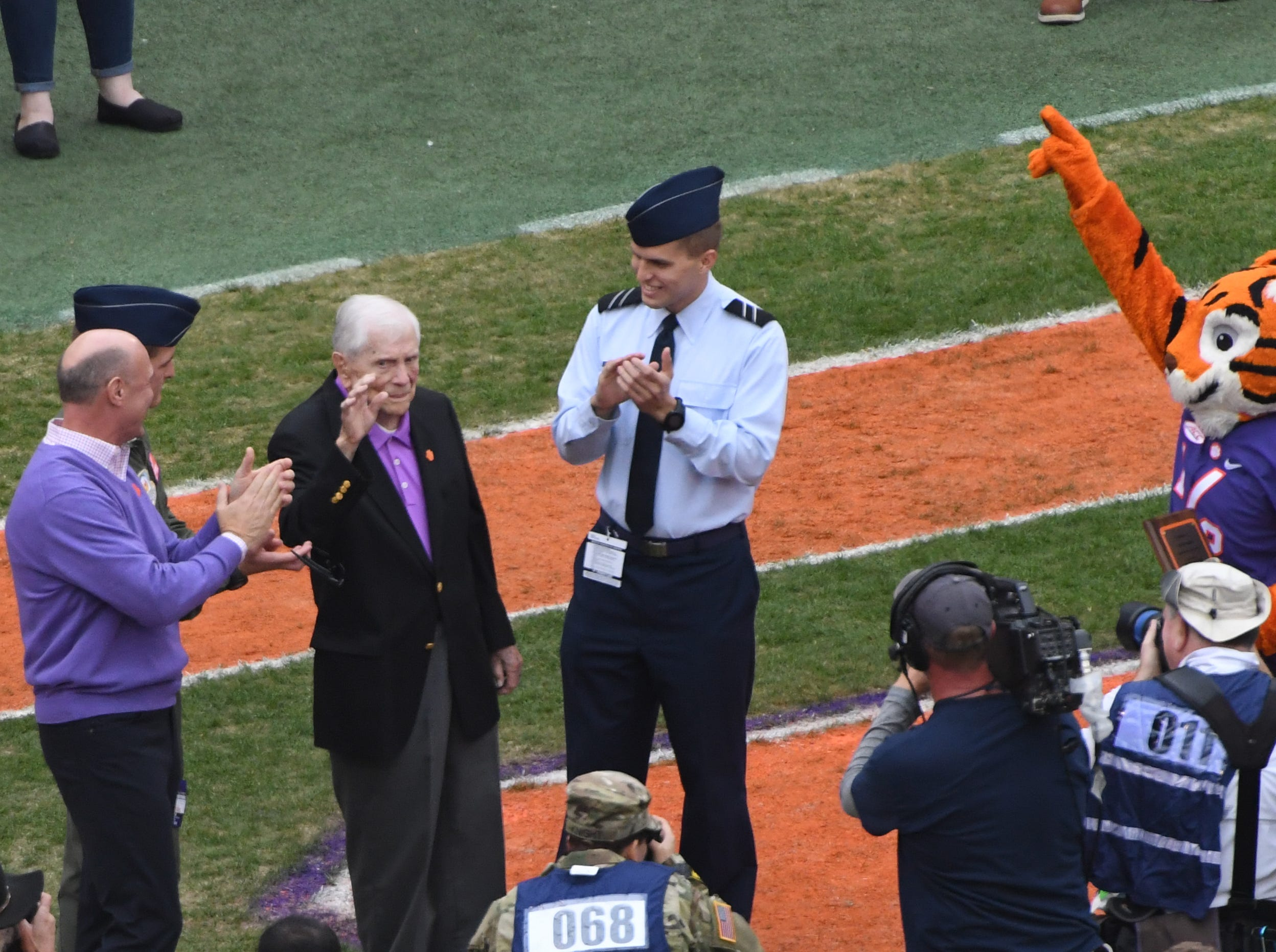 Col. Ben Skardon, 100-years old, a Clemson graduate and Bataan Death March survivor, waves as he is honored during Military Appreciation Day in Clemson on Saturday, November 17, 2017. President Jim Clements, left, joins the Tiger Cub, right, and others in the presentation during the first quarter in Memorial Stadium at Clemson on Saturday.