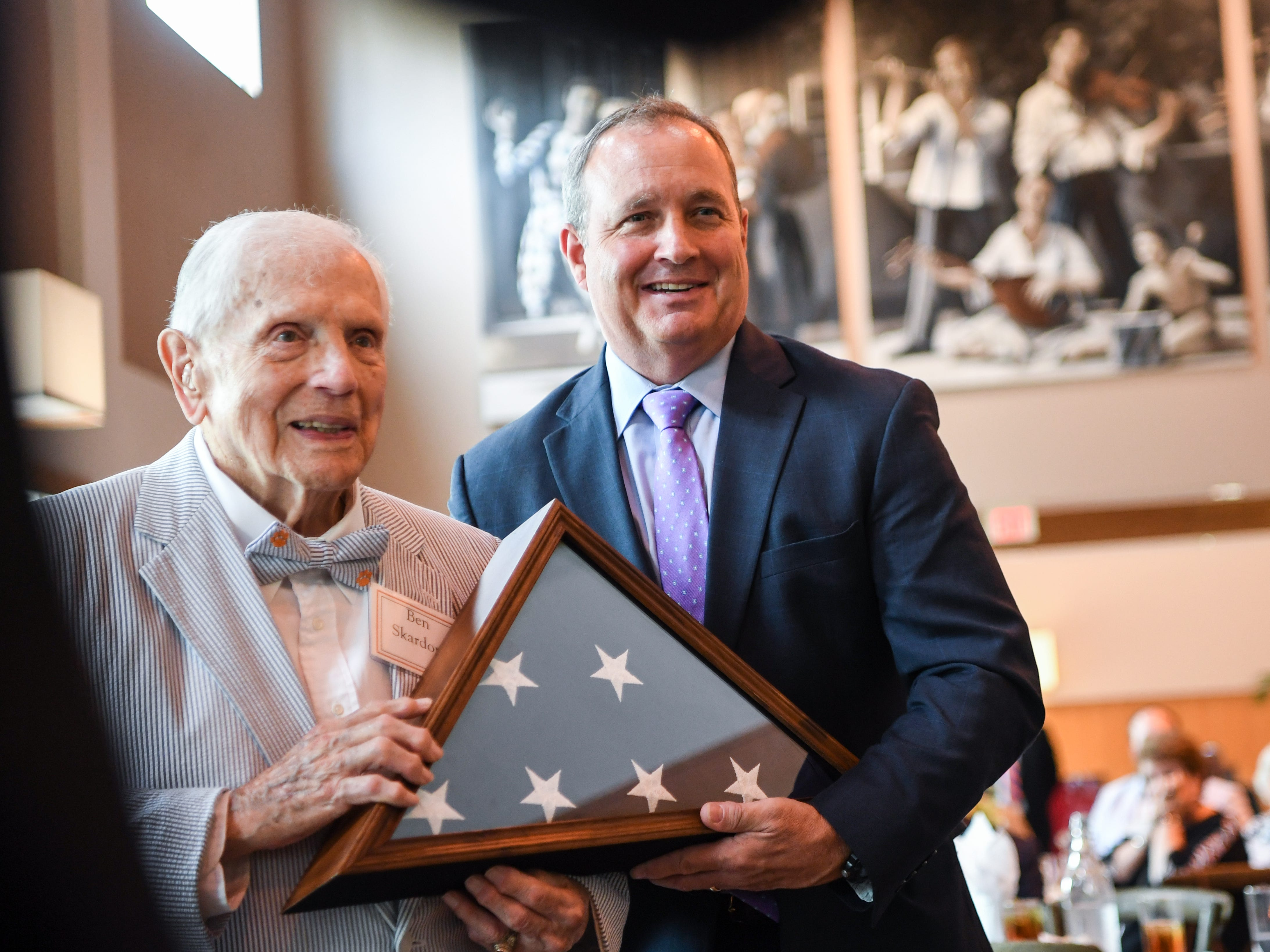 In 2017, Clemson graduate Col. Ben Skardon, left, is presented a a flag flown over the U.S. Capitol by U.S. Rep. Jeff Duncan, right, during his 100th birthday celebration at the Brooks Center in Clemson.