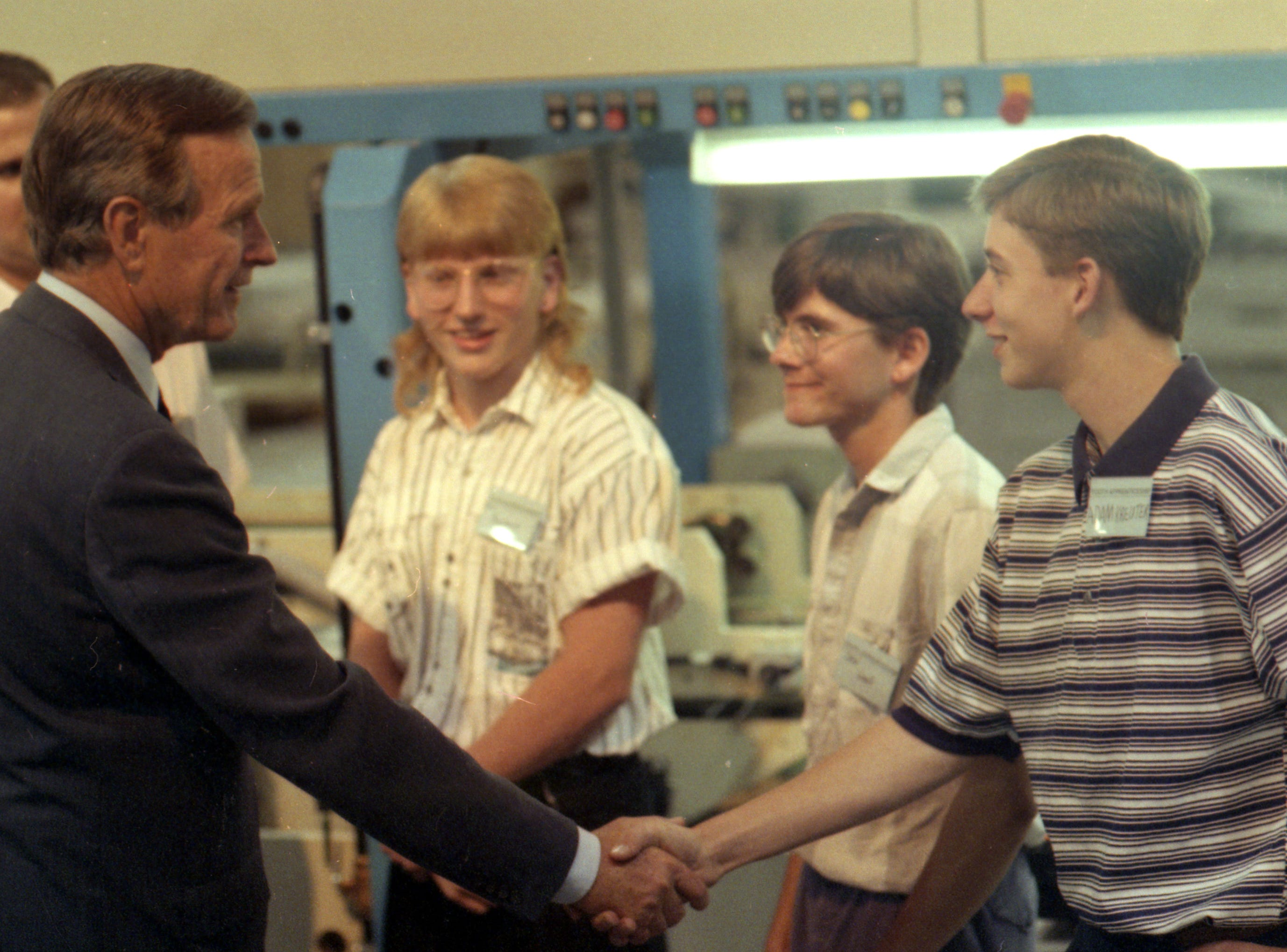 July 27, 1992. Adam Kreuter of Neenah shakes hands with President George H. W. Bush who met students at Outlook Graphics in the Town of Menasha. Post-Crescent photo by Mark Courtney