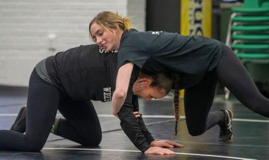 Raritan High School wrestler Jillian Acevedo (top) works with head coach Melissa Gardner in practice.
