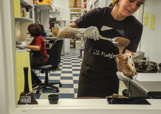 Christy Burkard of Suzi's Sweet Shoppe, a Middletown family-owned business, spoons chocolate into a boot mold. The family-owned business offers hand-dipped chocolates, gift baskets, party favors, and homemade fudge.