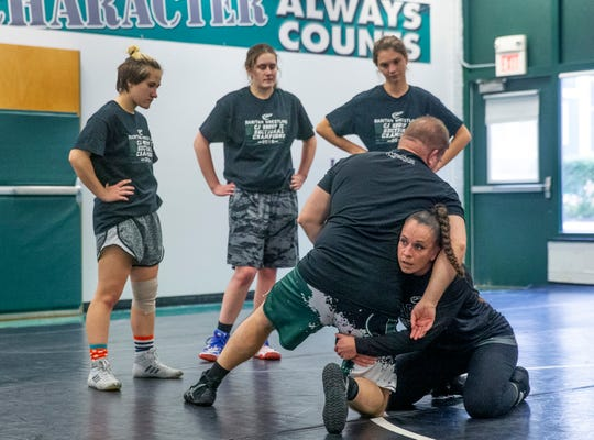 Coaches Robert Nucci and Melissa Gardner demonstrate some moves during practice. NJSIAA is offering wrestling for girls this year and they will participate in an all girls tournament at the end of the season. Raritan High School Wrestling is fielding nearly a  full girls team this year. While girls mostly practice separately from the boys, they are in a room next to the boys and frequent coaching sessions happen in the boys room to teach moves.