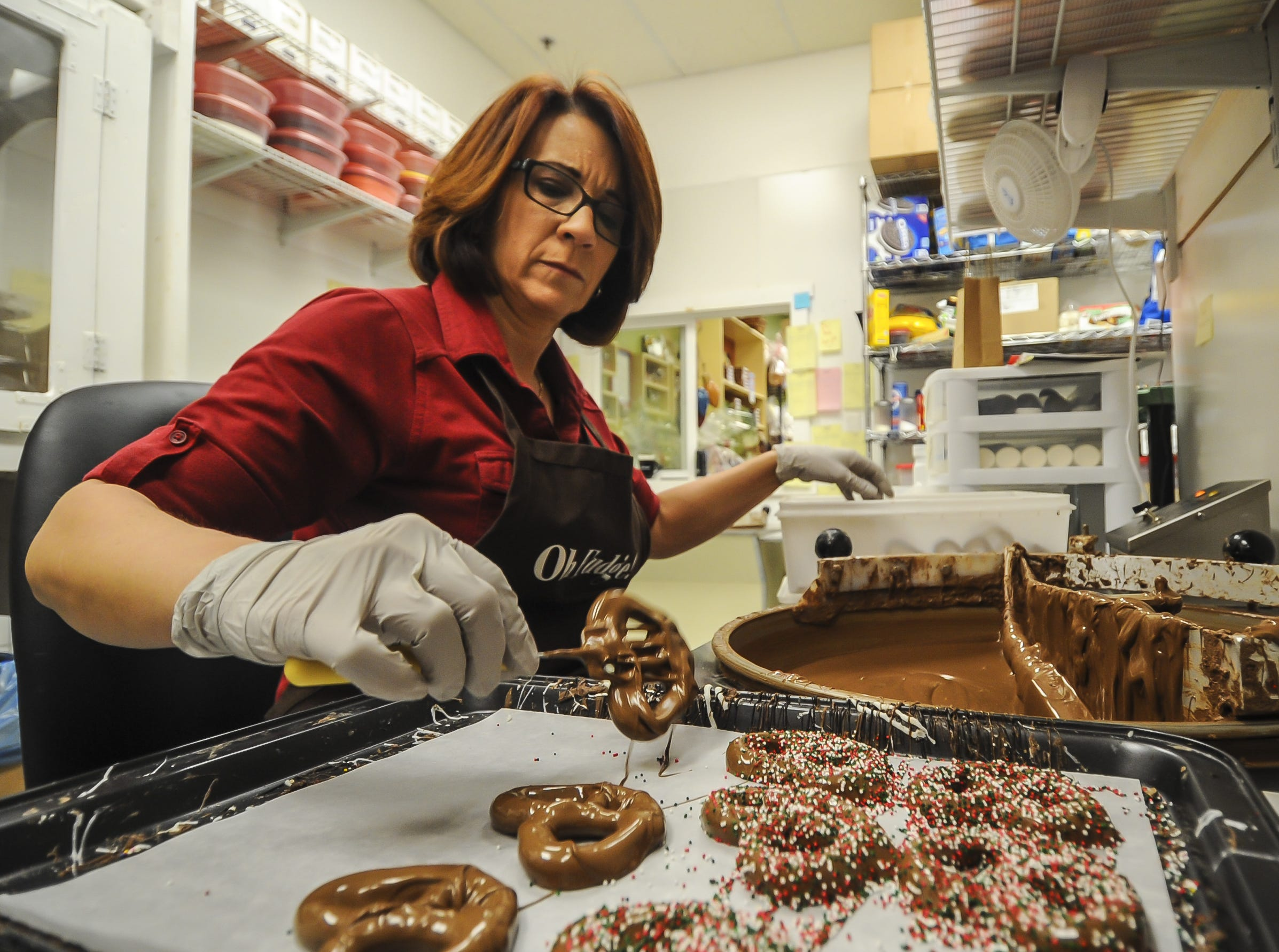 Susan Hordych, owner of Suzi's Sweet Shoppe, a Middletown family-owned business, places a pretzel dipped in chocolate from the dipping pot onto a tray. The family-owned business offers hand-dipped chocolates, gift baskets, party favors, and homemade fudge.