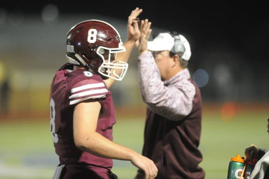 De Leon QB Kevin Yeager (8) high-fives his dad, Bearcats coach David Yeager, following a TD run in the first quarter of a Region II-2A Division I semifinal against Riesel at Wildcat Stadium in Whitney in 2018.
