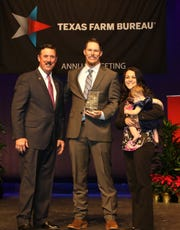 Russell Boening, Texas Farm Bureau president, with Justin and Lindsay Hannsz, the organizations' outstanding young farmers of the year.