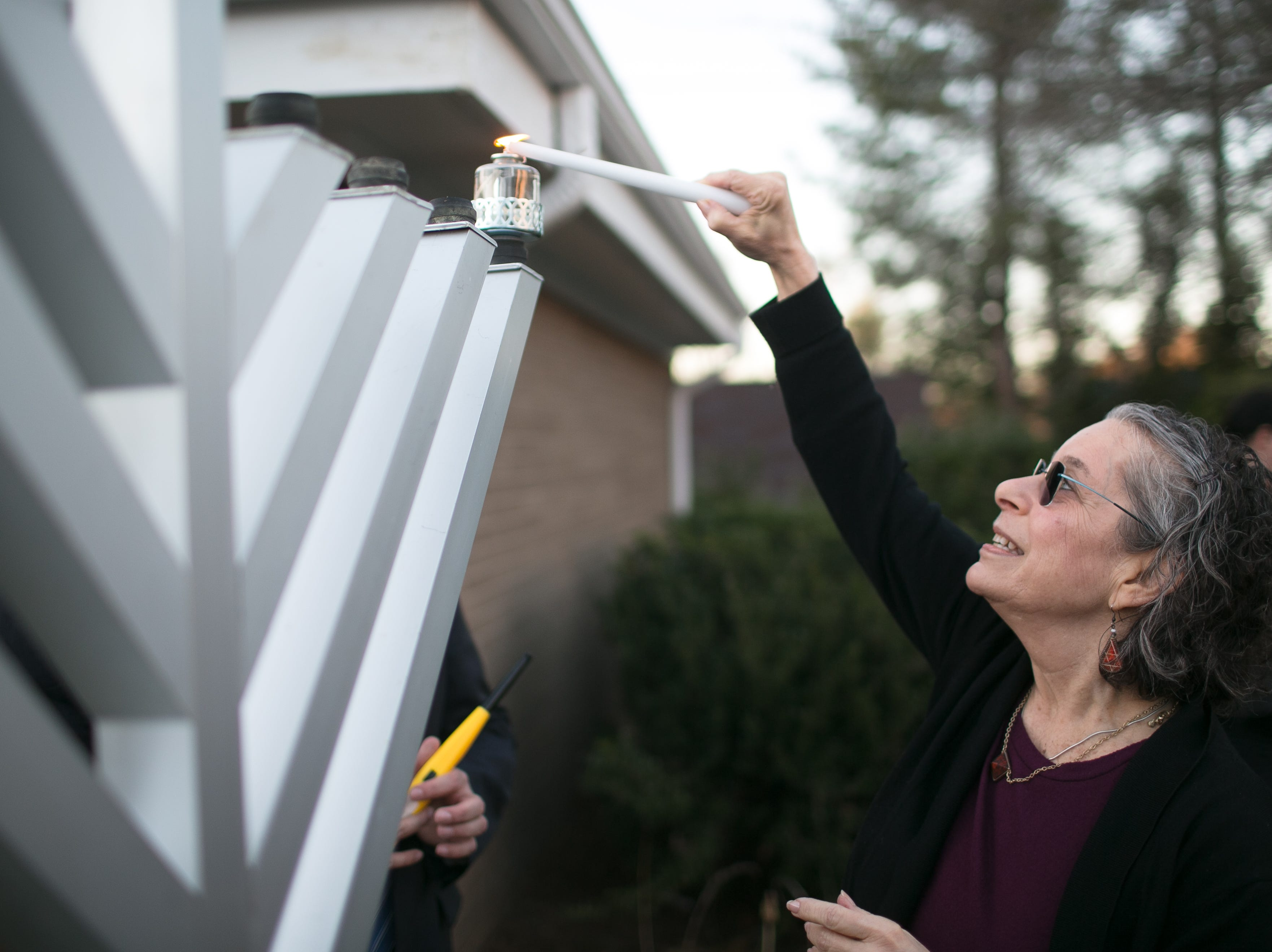 Alison Gilreath of Jewish Family Services lights the 8-foot Giving Menorah during Chanukah Live!, Asheville's community Hanukkah celebration. The event was held at the Chabad House on Dec. 2, 2018, in conjunction with the grand opening of their new facility on McDowell Street.