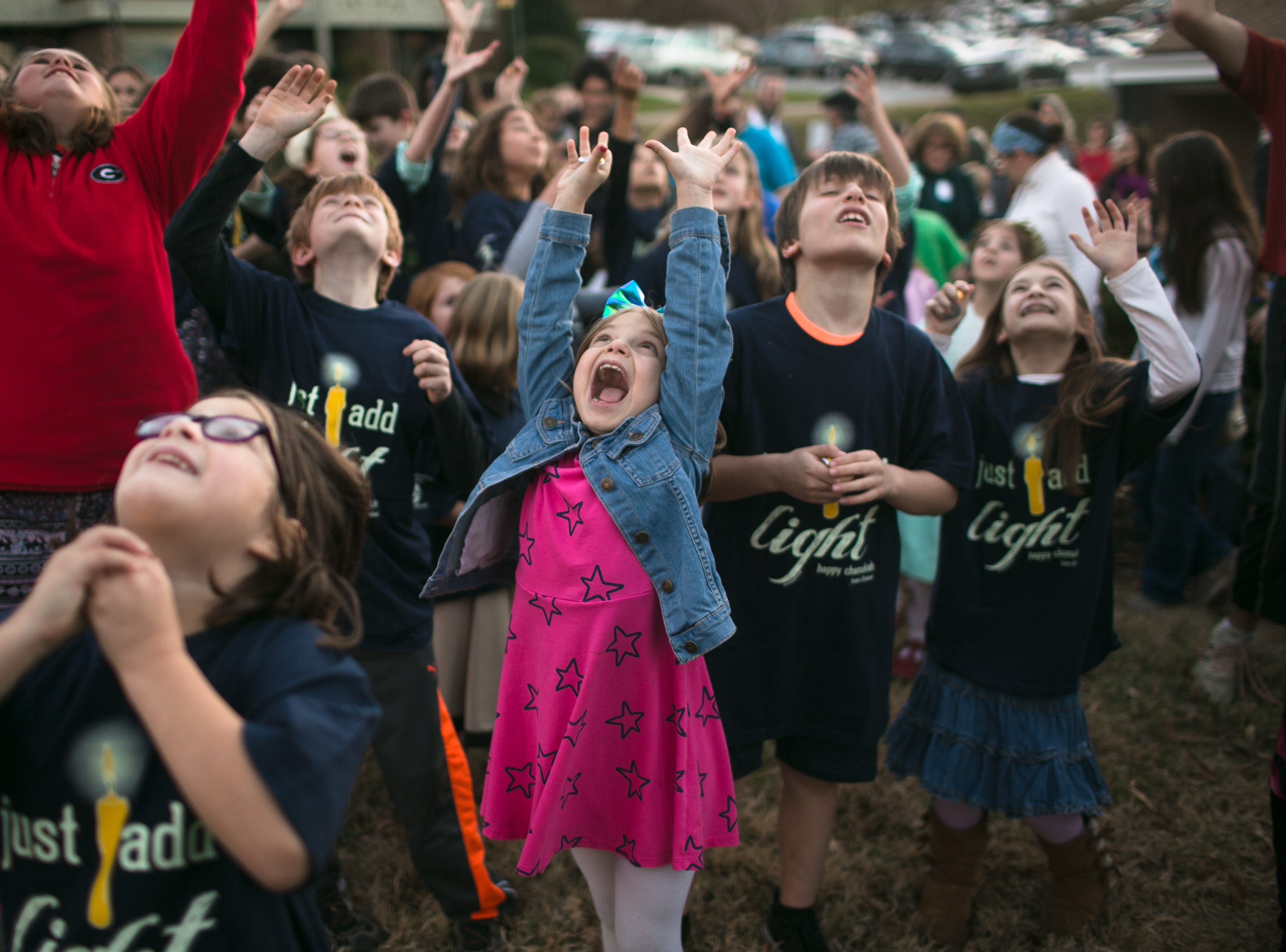 Sadie Whitehill, center, throws her hands up for chocolate gold coins during the Great Gelt Drop, which was facilitated by the Asheville Fire Department during Chanukah Live!, Asheville's community Hanukkah celebration. The event was at the Chabad House on Dec. 2, 2018, in conjunction with the grand opening of their new facility on McDowell Street.