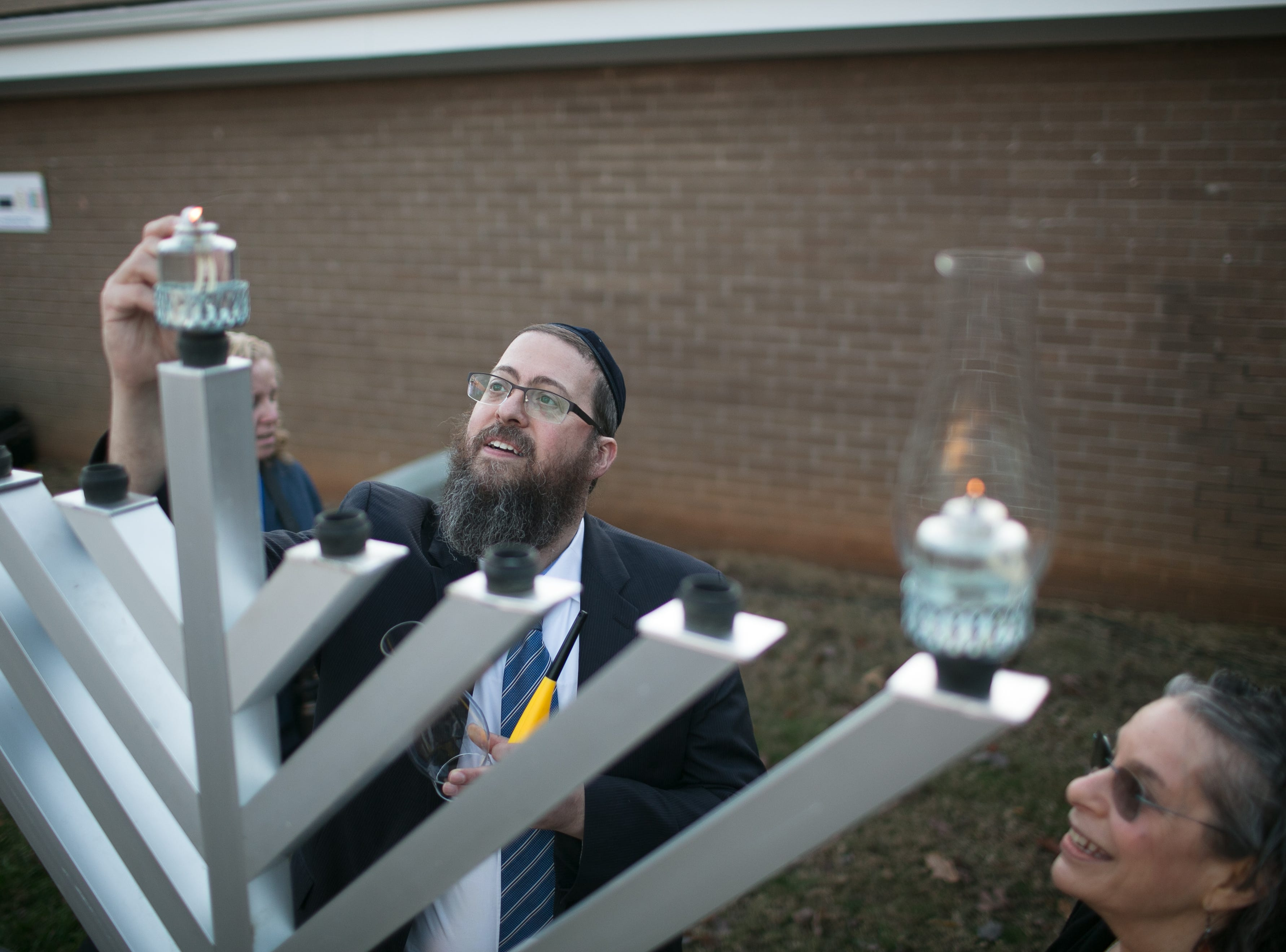 Chabad House Rabbi Shaya Susskind lights the 8-foot Giving Menorah alongside Alison Gilreath during Chanukah Live!, Asheville's community Hanukkah celebration. The event was held at the Chabad House on Dec. 2, 2018, in conjunction with the grand opening of their new facility on McDowell Street.