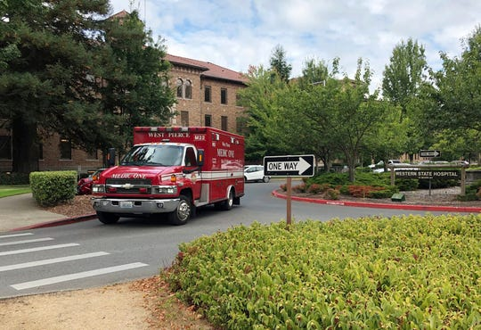 FILE - In this Aug. 30, 2018, file photo, an ambulance leaves Western State Hospital in Lakewood, Wash. An Associated Press investigation has found assaults on staff and patients at Washington state's largest psychiatric hospital are on the rise. It also found that disability claims by injured staff topped $5 million in less than three years, and the number of days missed due to injuries has more than doubled since 2016. (AP Photo/Martha Bellisle, File)