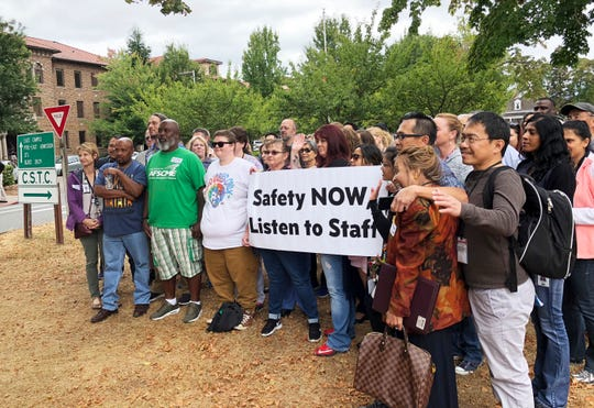 FILE - In this Aug. 30, 2018 file photo, workers rally demanding changes to the way officials assign dangerous patients to wards at Western State Hospital in Lakewood, Wash. An Associated Press investigation has found assaults on staff and patients at Washington state's largest psychiatric hospital are on the rise. It also found that disability claims by injured staff topped $5 million in less than three years, and the number of days missed due to injuries has more than doubled since 2016. (AP Photo/Martha Bellisle, File)