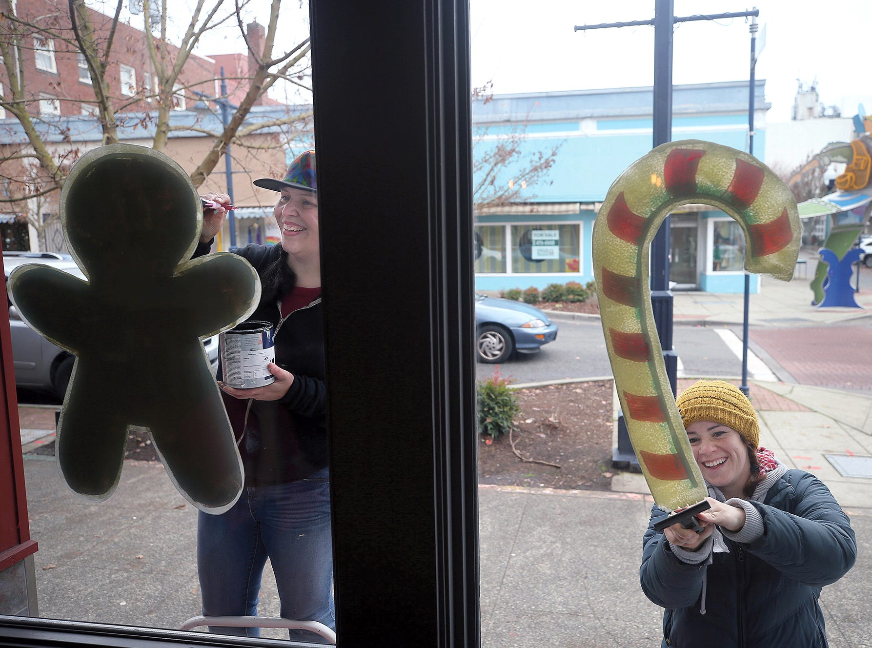 Window painter Danielle Rimbert, left, of Port Orchard and helper Christina Dempsey paint Christmas figures on the windows at the Hot Java Cafe at Fourth Street and Pacific Ave. in downtown Bremerton on Monday, December 3, 2018.