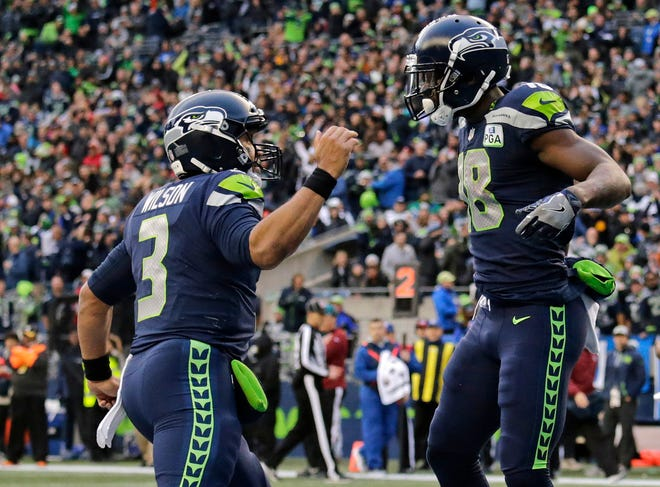 Seattle Seahawks quarterback Russell Wilson (left) greets wide receiver Jaron Brown after the two connected for a touchdown.