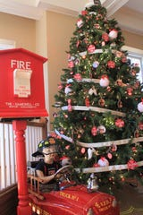 The Black Mountain Fire Department's entry in Deck the Trees at the Monte Vista Hotel features ornaments with faces of current firefighters and their years of service.