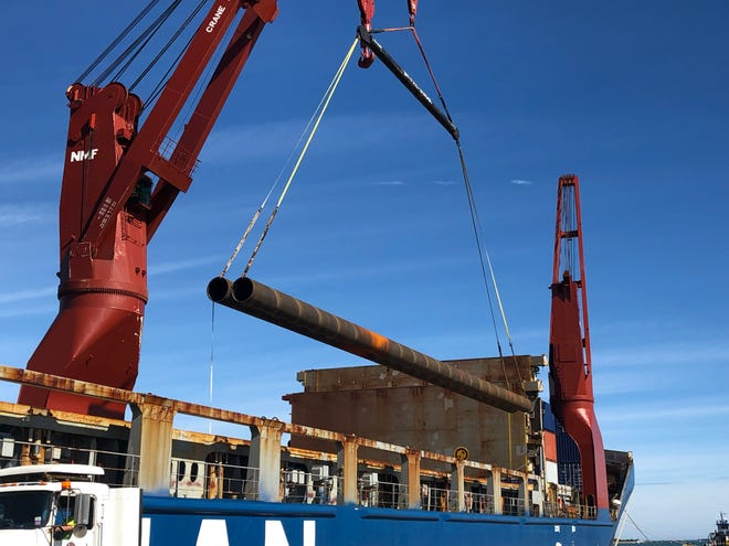 Workers unload 36-inch diameter steel pipes at Port Canaveral that will be used to anchor the waterside bulkhead wall at Port Canaveral's new Cruise Terminal 3. (Photo courtesy of Canaveral Port Authority.)