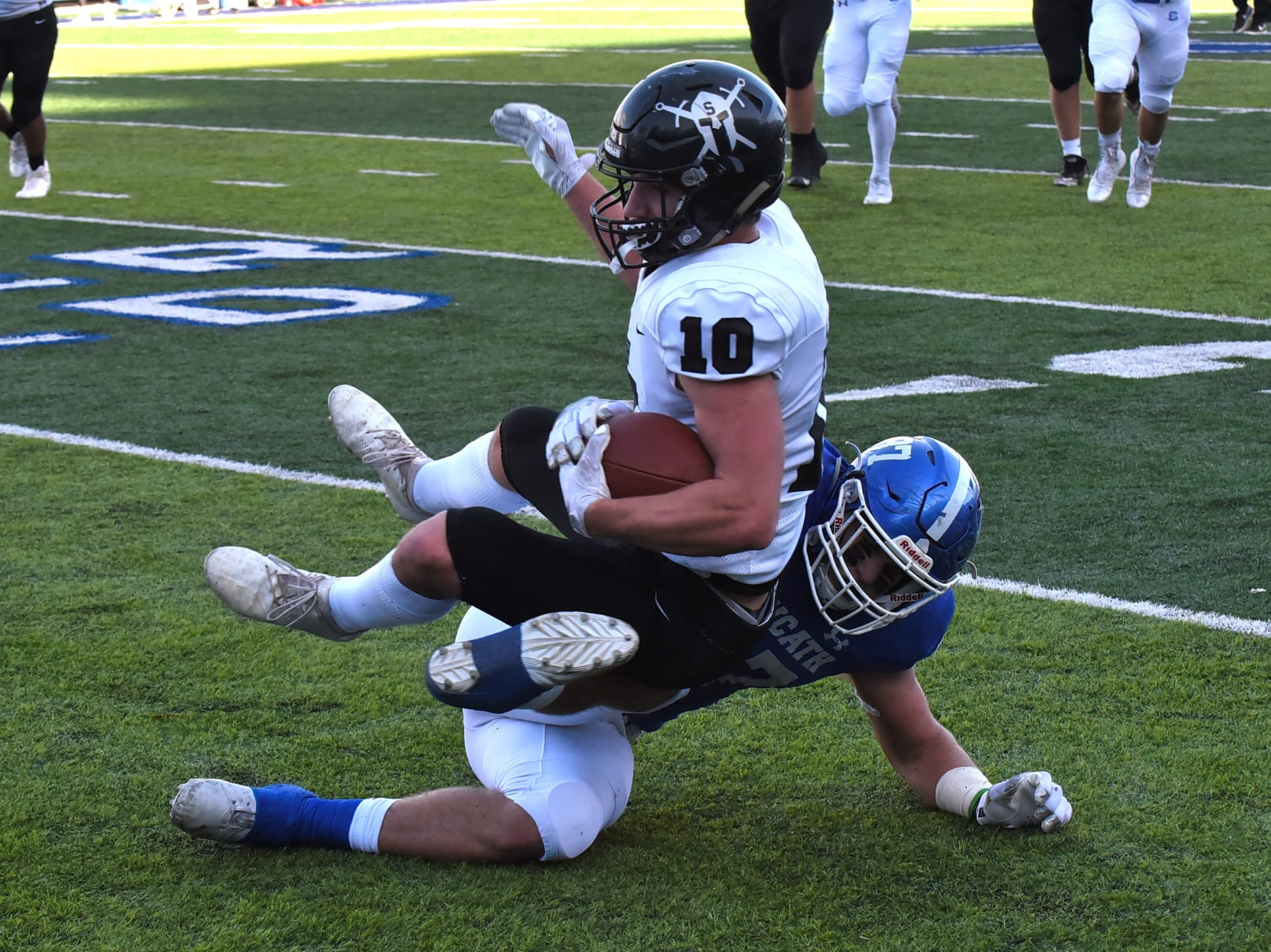 Covington Catholic's Michael Mayer drops Clayton Bush (10) of South Warren after making a first down catch for the Spartans in the 2018 KHSAA 5A State Football Championship, December 2, 2018.