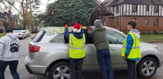 Scouts from Mariemont Boy Scout Troop 149 secure a tree atop a vehicle.