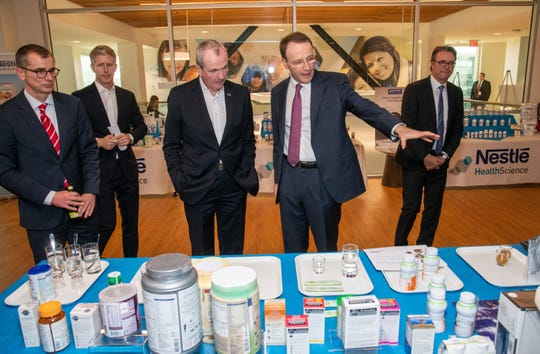 Greg Behar, CEO, Nestlé Health Science , Gov. Phil Murphy, Mark Schneider, CEO, Nestlé and Thomas Hauser, senior vice president , Head of Global Product & Technology Development, sample products at Nestlé's  Product Technolog Center in Bridgewater.