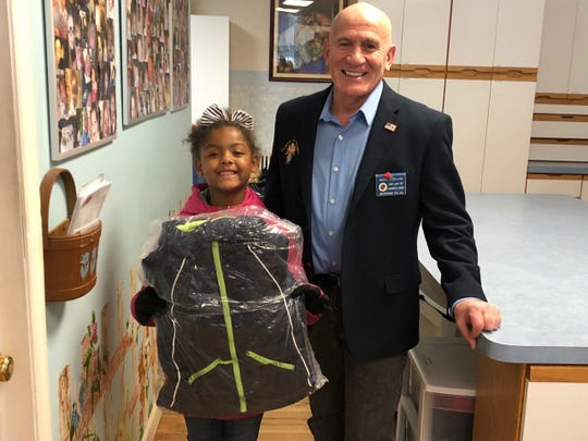 A young girl proudly shows off a coat she received to Mike DaSilva of the Knights of Columbs Council 6930 Our Lady of Lourdes, Whitehouse Station. The Knights presented charitable donations to  local agencies.