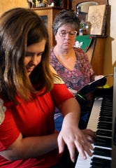 Piano teacher Vickie Davis works with one of her students at her home near Coshocton.