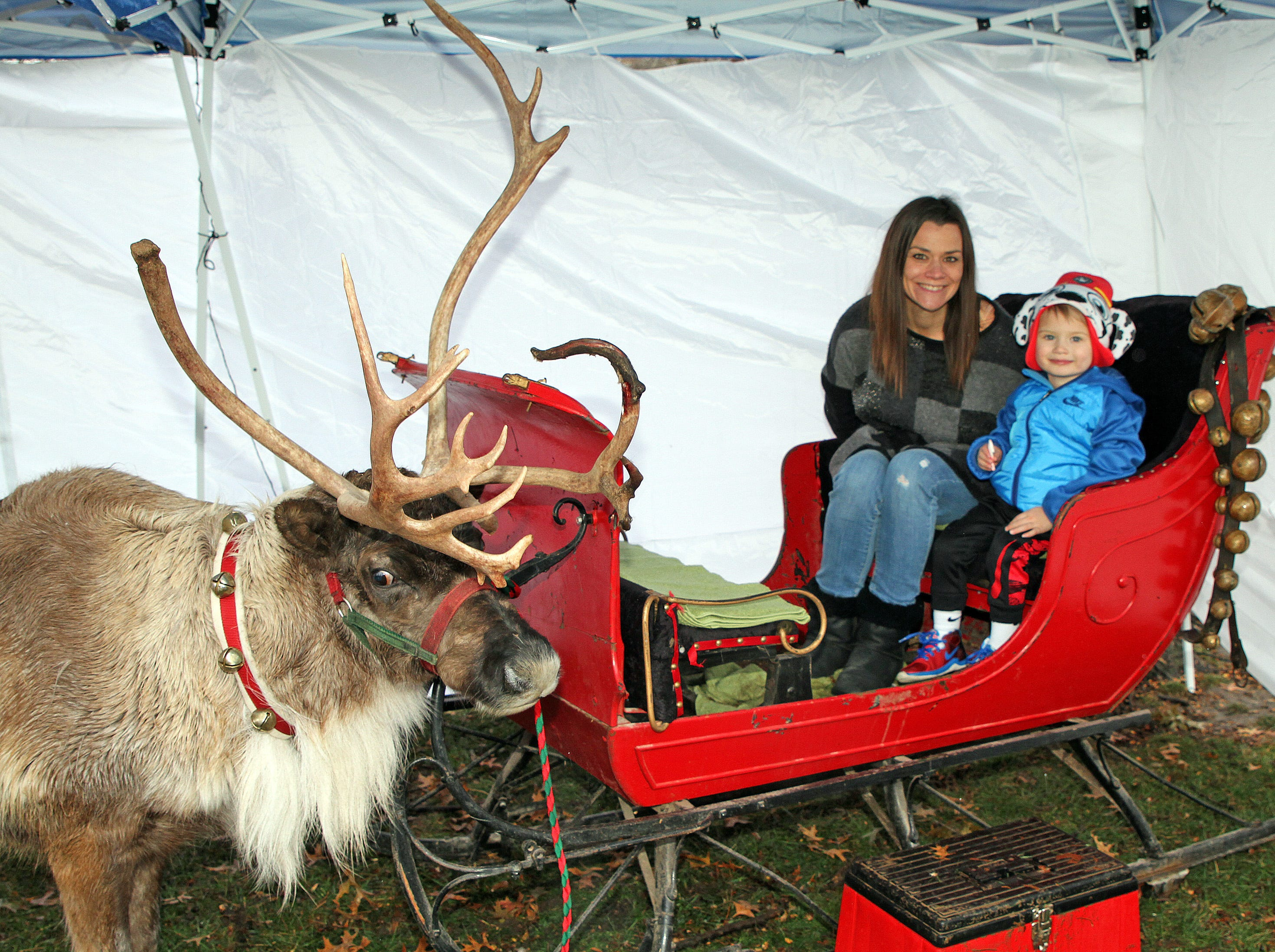 Zayden, 3, and Jennifer Wulkow of Urbandale stop for a picture with Rudy the Reindeer during UCAN's third annual Light Up Urbandale on Sunday, Dec. 2, 2018 at Lions Park in Urbandale. Holiday festivities included a visit from Santa, crafts, goodies, official tree lighting ceremony, live reindeer and entertainment. This event helps raise awareness and support for the Urbandale Community Action Network Holiday Helping Hands Programs for families, kids, teens and seniors in need.