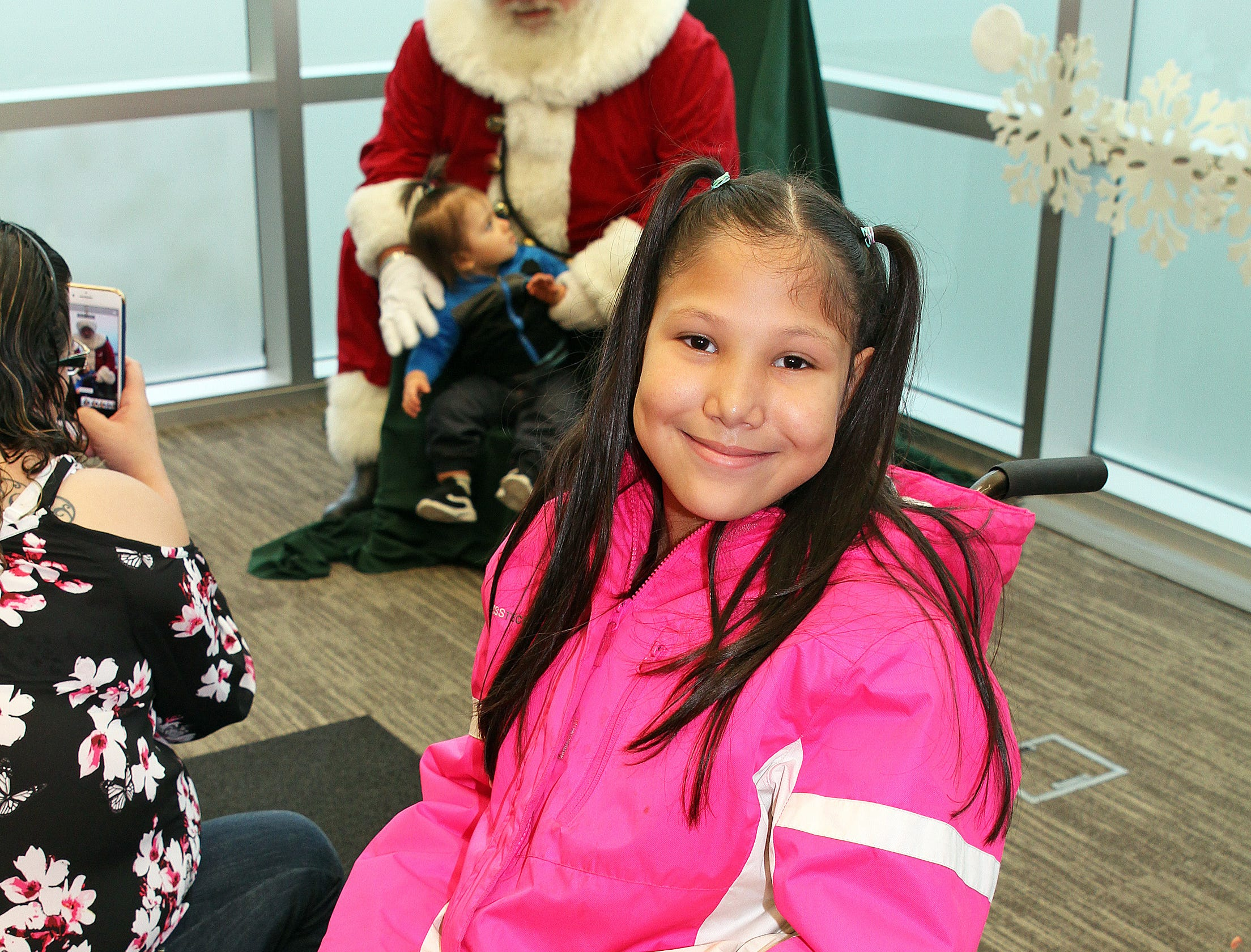Danica Mota, 9, of Johnston enjoyed her visit with Santa during Holidays in Johnston on Saturday, Dec. 1, 2018 at the Johnston Public Library featuring a gingerbread house contest, cookie decorating, holiday music performed by the Johnston Middle School Ninth Grade Chamber Choir, story time and Santa.
