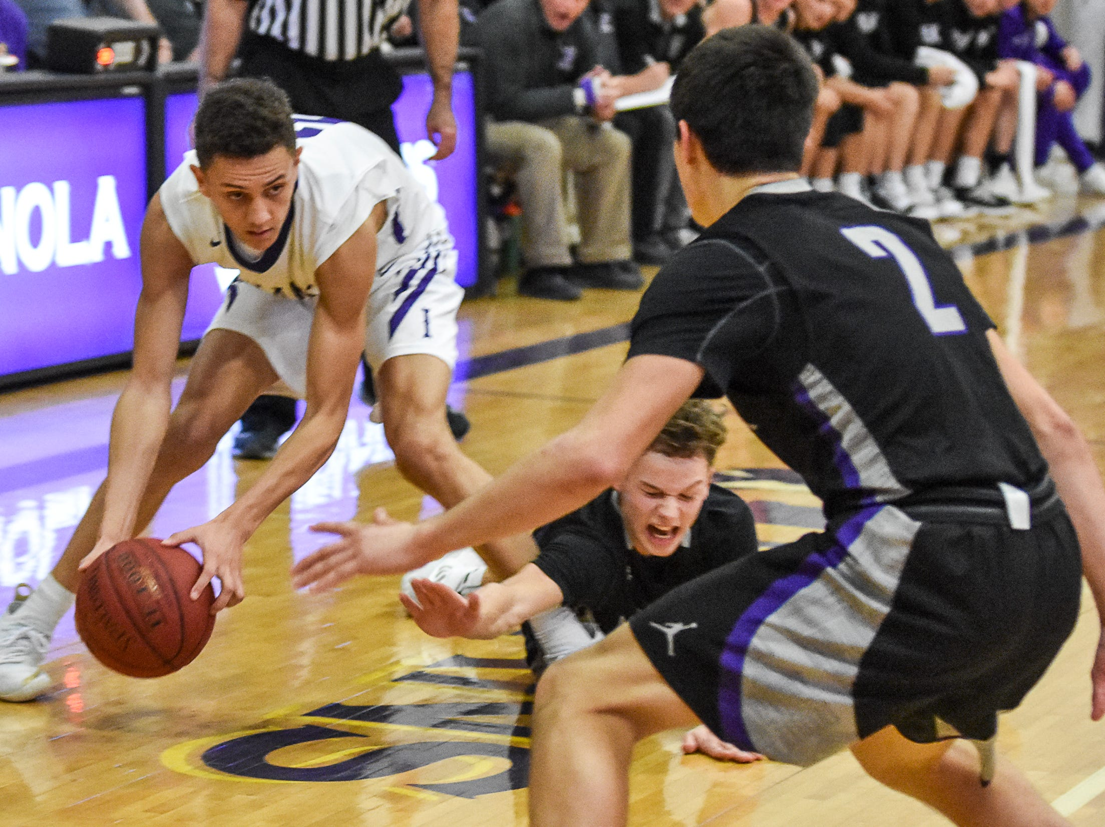 Indianola's Evan Gauger grabs a loose ball as Norwalk's Bowen Born goes to the floor. The Indianola boys slipped to 1-1 on the season with a 65-48 home loss to Norwalk on Nov. 30, 2018.