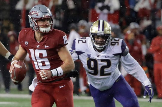 Washington State quarterback Gardner Minshew (16) scrambles under pressure from Washington defensive lineman Jaylen Johnson, right, during the first half of an NCAA college football game, Friday, Nov. 23, 2018, in Pullman, Wash. (AP Photo/Ted S. Warren)