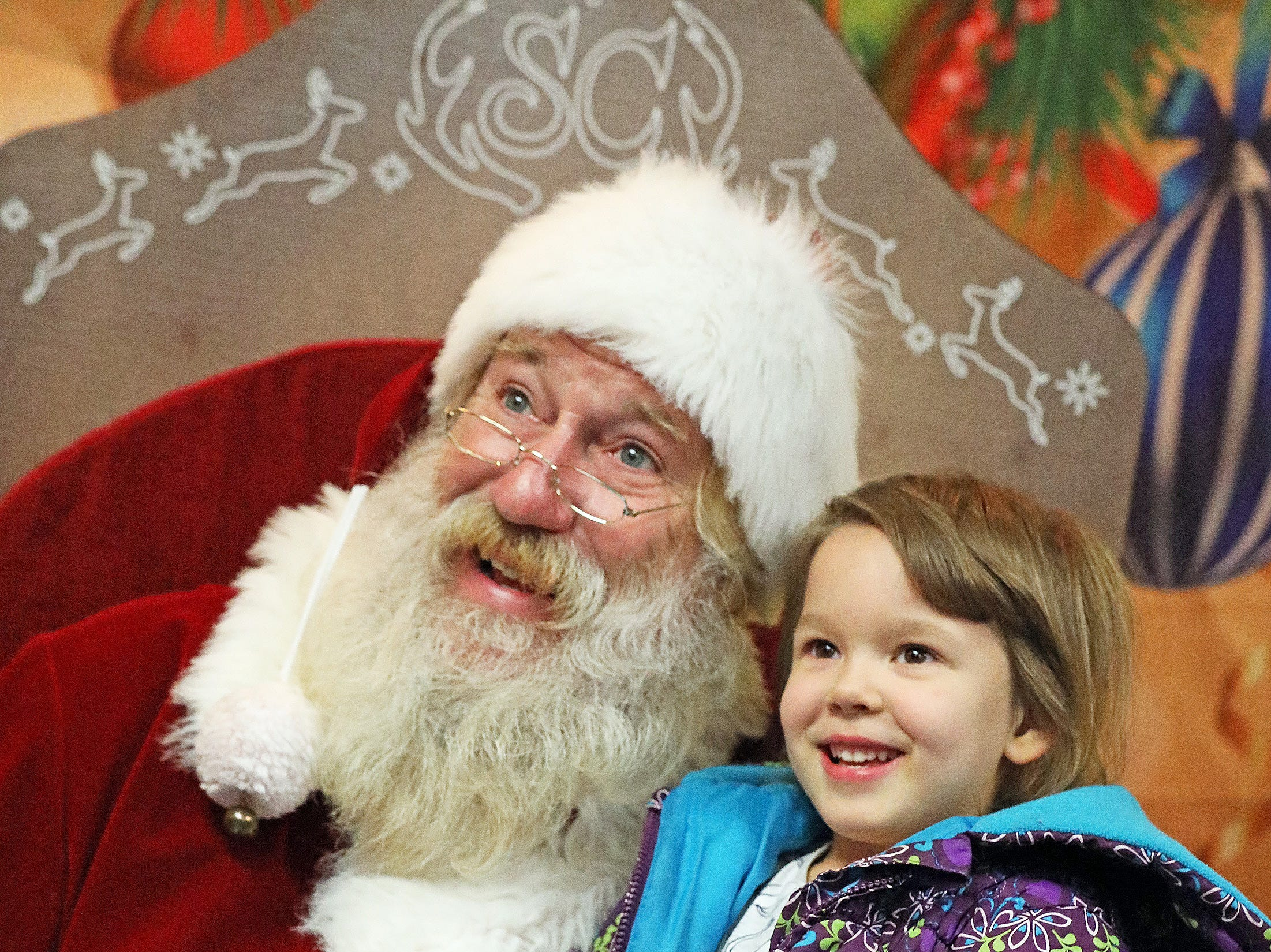 Santa and Norah Burrier, 5, of Urbandale smile as Burrier's dad takes her picture during UCAN's third annual Light Up Urbandale on Sunday, Dec. 2, 2018 at Lions Park in Urbandale. Holiday festivities included a visit from Santa, crafts, goodies, official tree lighting ceremony, live reindeer and entertainment. This event helps raise awareness and support for the Urbandale Community Action Network Holiday Helping Hands Programs for families, kids, teens and seniors in need.