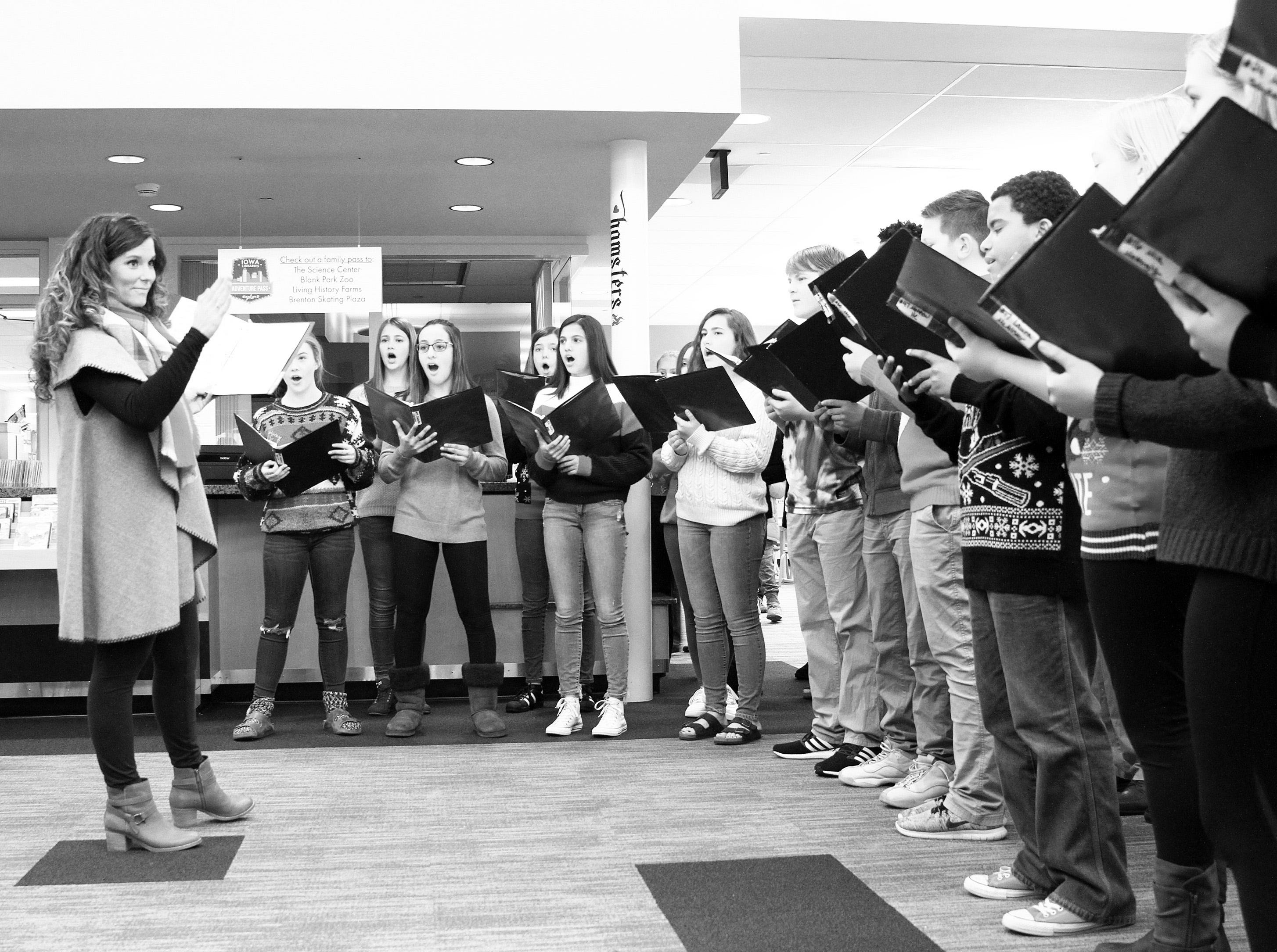 Vocal Music Teacher Laura Grimm directs the Johnston Middle School Ninth Grade Chamber Choir during Holidays in Johnston on Saturday, Dec. 1, 2018 at the Johnston Public Library featuring a gingerbread house contest, cookie decorating and Santa.