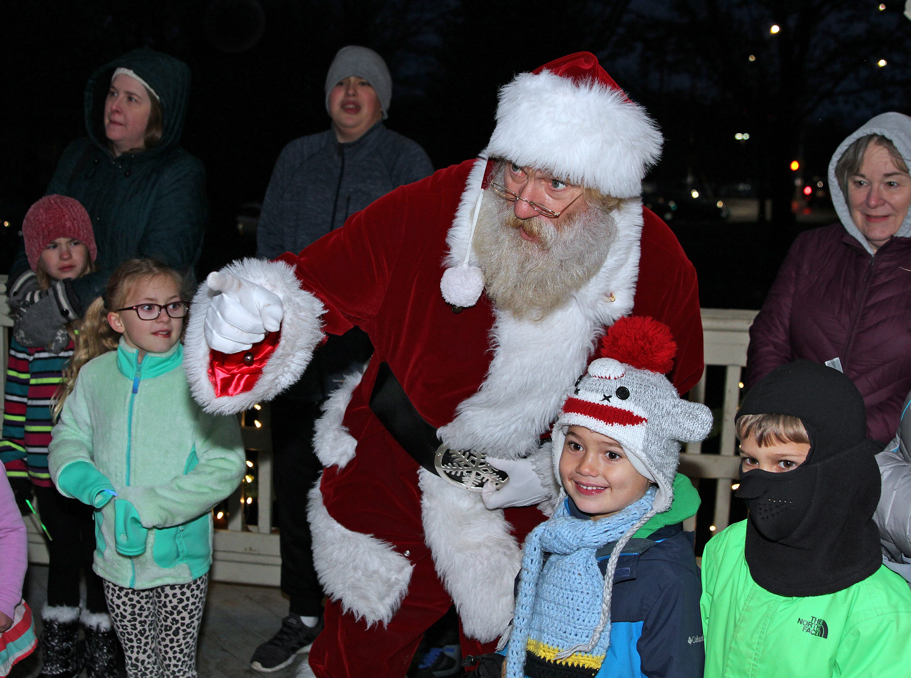 Santa points out the bell ringers to the kids during UCAN's third annual Light Up Urbandale on Sunday, Dec. 2, 2018 at Lions Park in Urbandale. Holiday festivities included a visit from Santa, crafts, goodies, official tree lighting ceremony, live reindeer and entertainment.