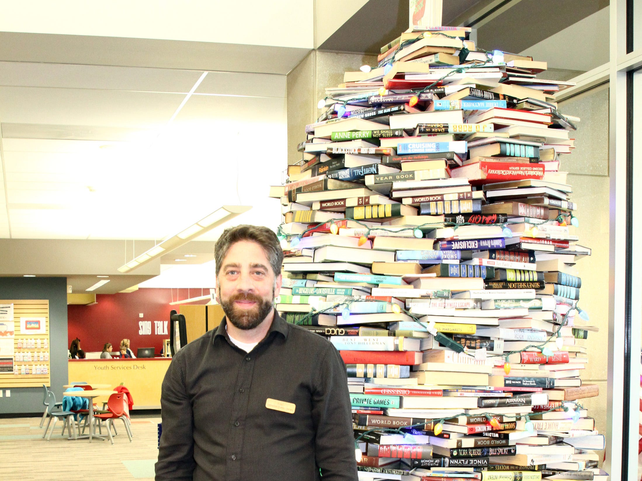 Library Director Eric Melton stands by the book tree during Holidays in Johnston on Saturday, Dec. 1, 2018 at the Johnston Public Library featuring gingerbread house contest, cookie decorating, story and craft time and Santa.