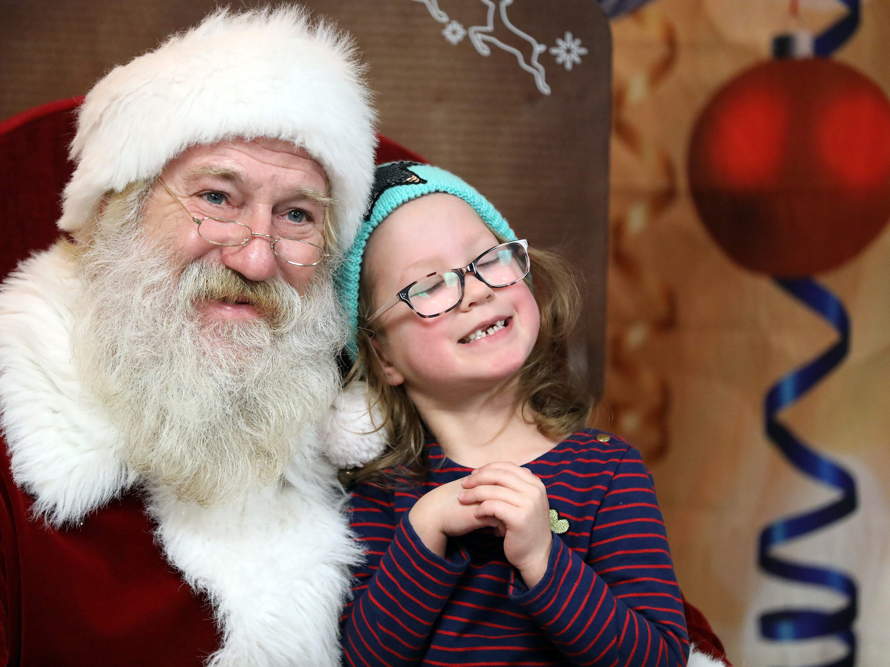 Eve Crow, 6, of Urbandale enjoys her time with Santa during UCAN's  third annual Light Up Urbandale on Sunday, Dec. 2, 2018 at Lions Park in Urbandale. Holiday festivities included a visit from Santa, crafts, goodies, official tree lighting ceremony, live reindeer and entertainment.