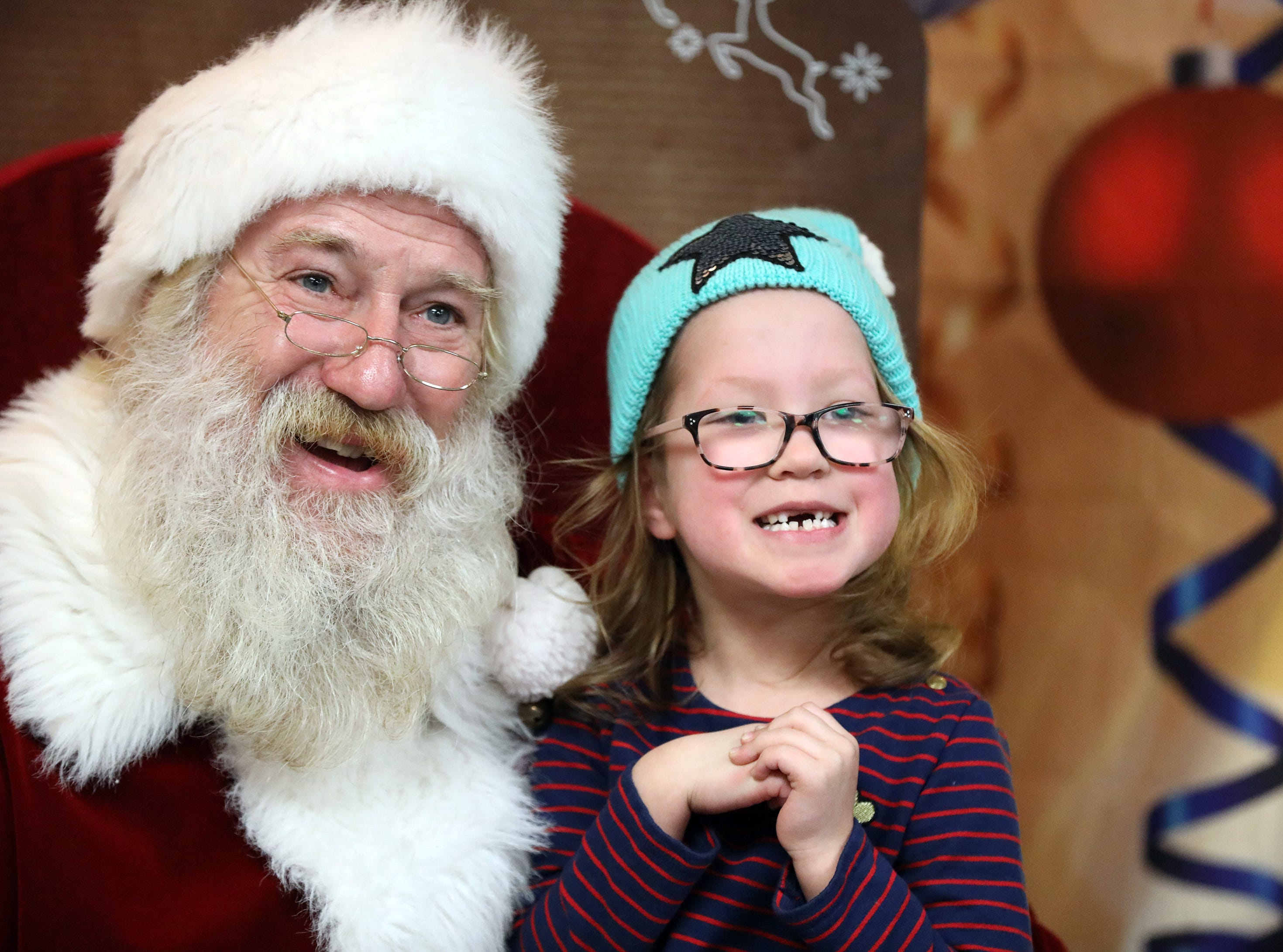 Santa and Eve Crow, 6, of Urbandale smile as Crow's parents take a picture during UCAN's  third annual Light Up Urbandale on Sunday, Dec. 2, 2018 at Lions Park in Urbandale. Holiday festivities included a visit from Santa, crafts, goodies, official tree lighting ceremony, live reindeer and entertainment.